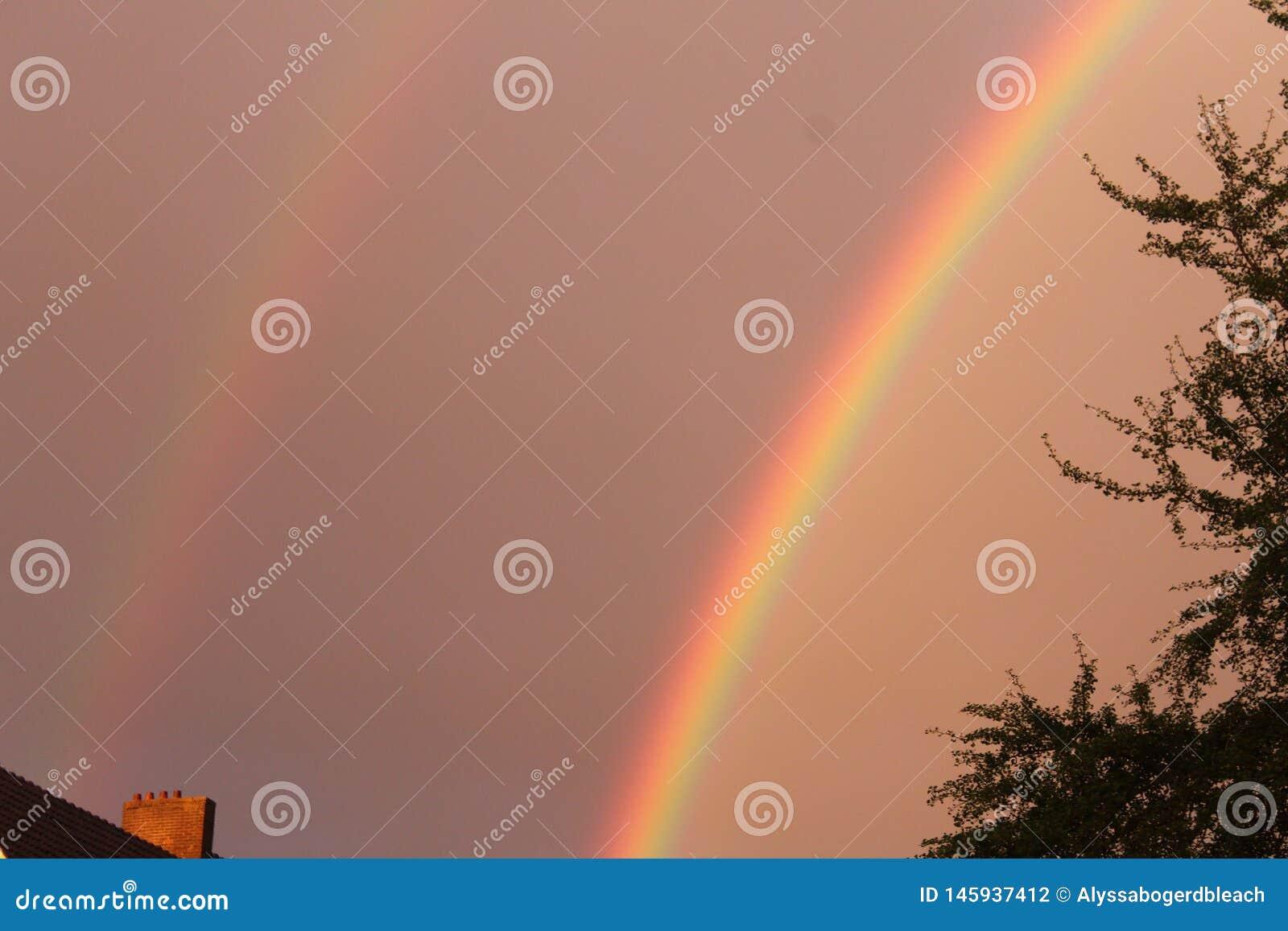 Arco-íris brilhante dobro com um céu e um telhado tormentosos
