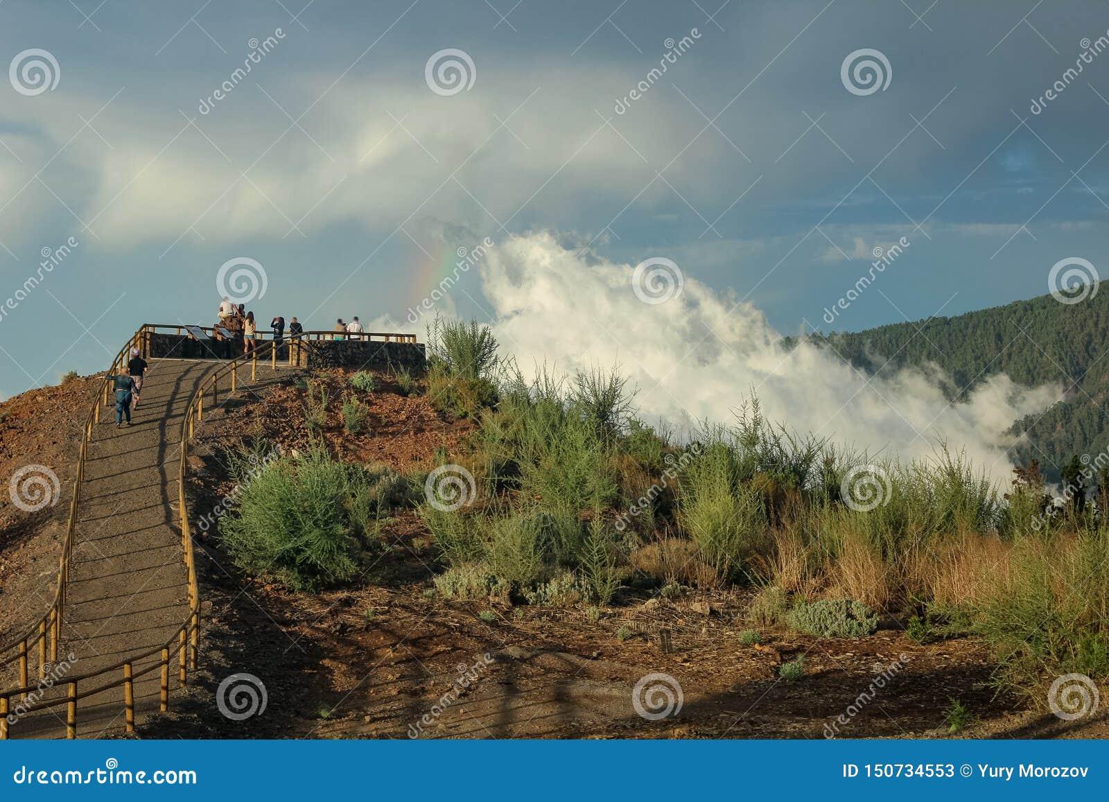 Arco-íris sobre a floresta, o fenômeno da natureza, rochas e árvores, cores brilhantes no arco-íris, chuva e céu nebuloso