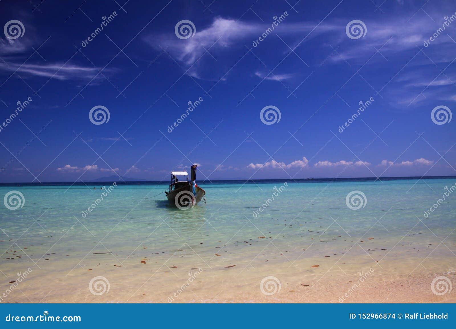 Arco aislado del barco del longtail en el agua poco profunda de la turquesa debajo del cielo azul con pocas nubes de cirro en la