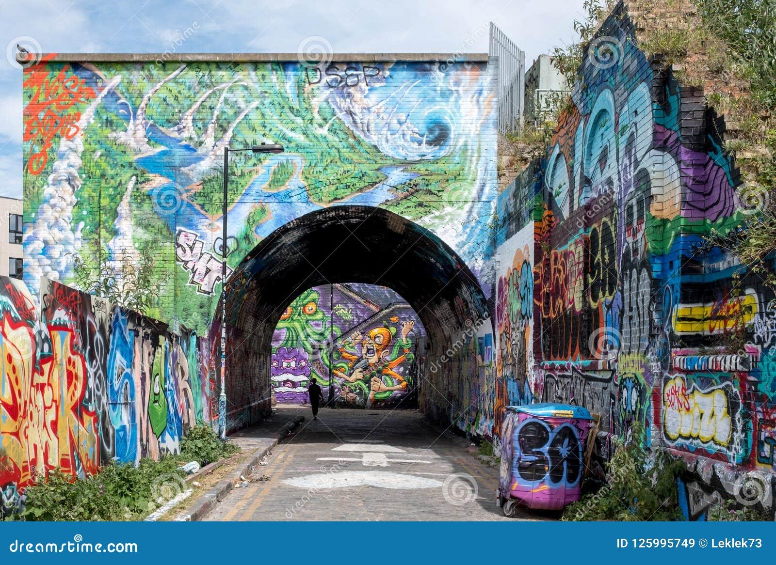 Arco da rua de Pedley, Shoreditch, Londres do leste Corredor pedestre sob a linha railway perto da pista do tijolo, coberta em gr
