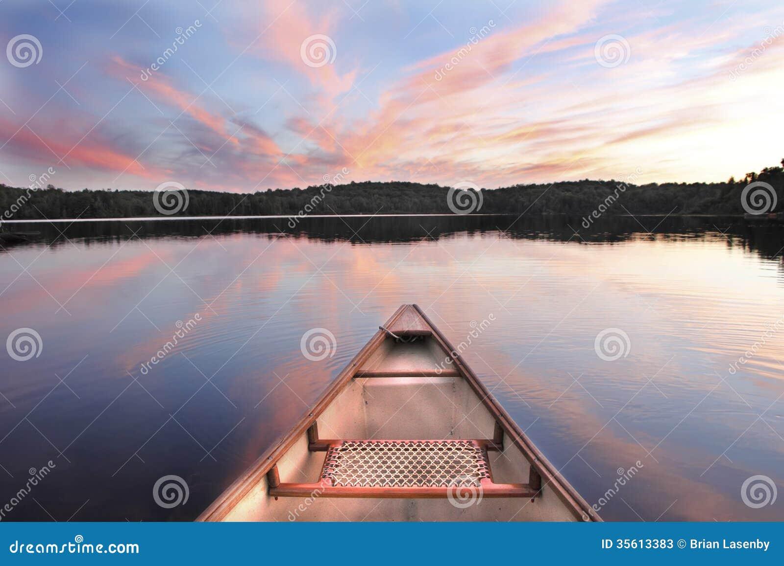 Arco de la canoa en un lago en la puesta del sol