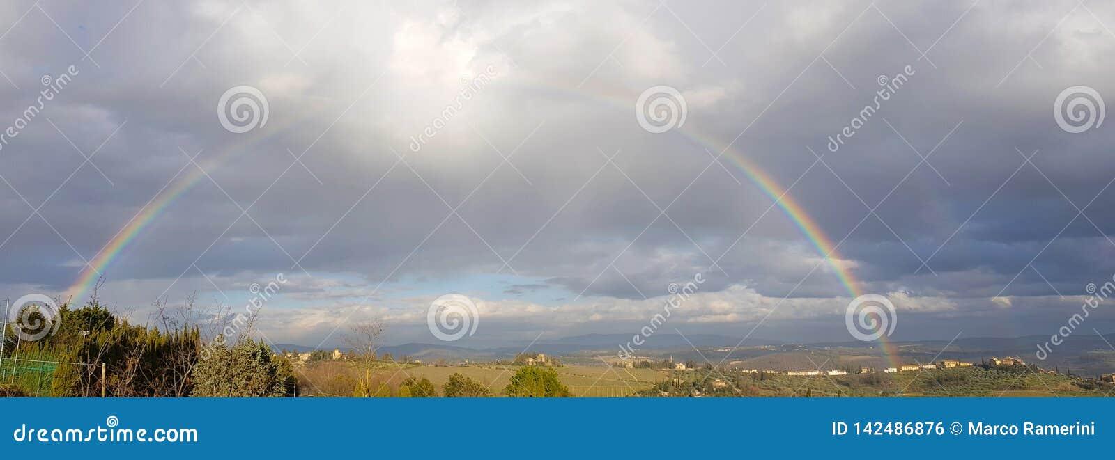Arco iris completo espectacular sobre las colinas de Chianti, Toscana, Italia