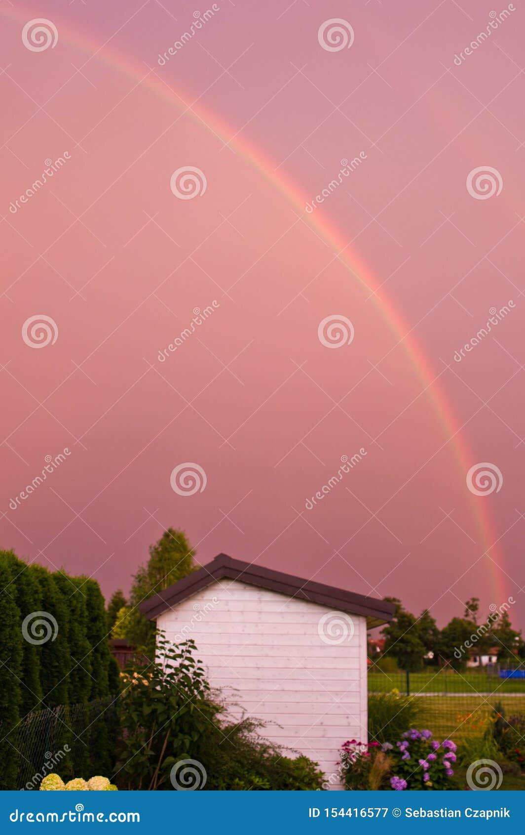 Arco iris doble sobre un jardín en color rosado