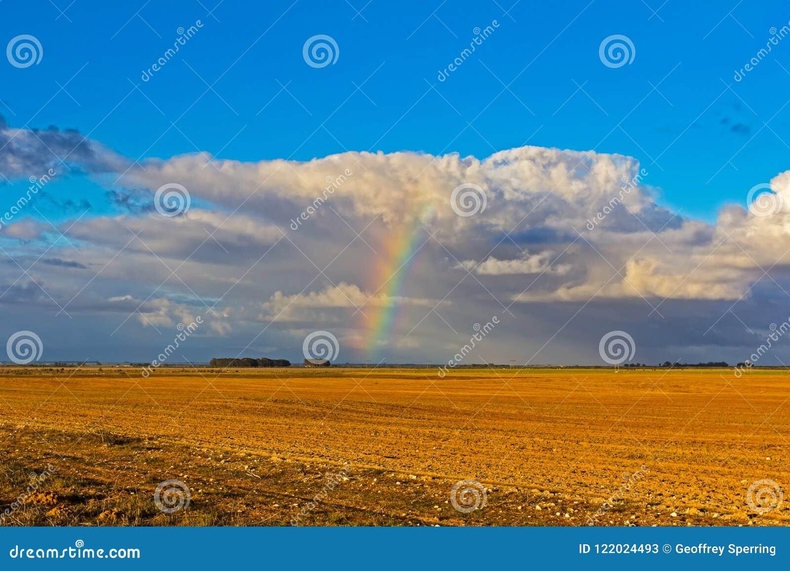 Arco iris y nubes sobre campo arado