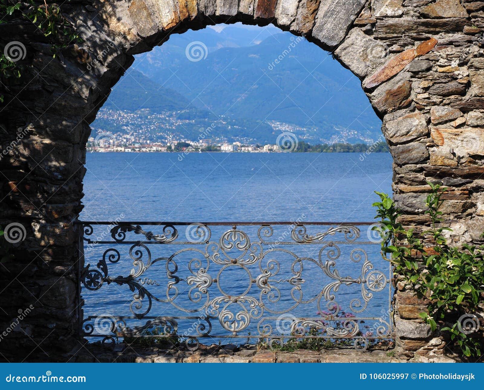 Arco pedregoso en la isla de Brissago en Suiza con la opinión alpina escénica sobre el lago suizo Maggiore