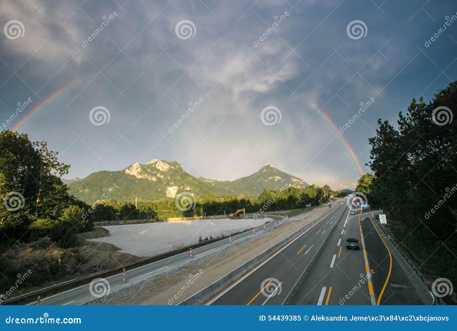Arcobaleno sopra le montagne e la strada principale dell alpe