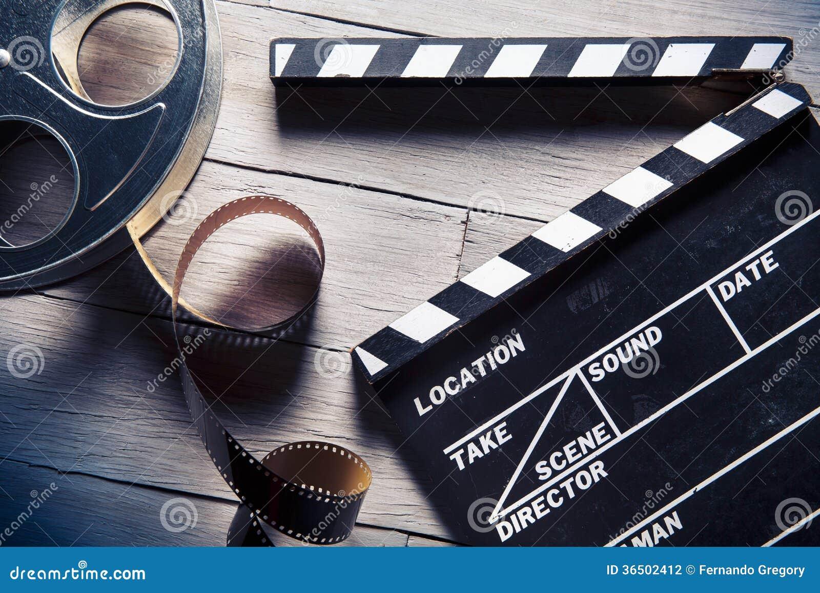Ardósia do filme e carretel de filme na madeira