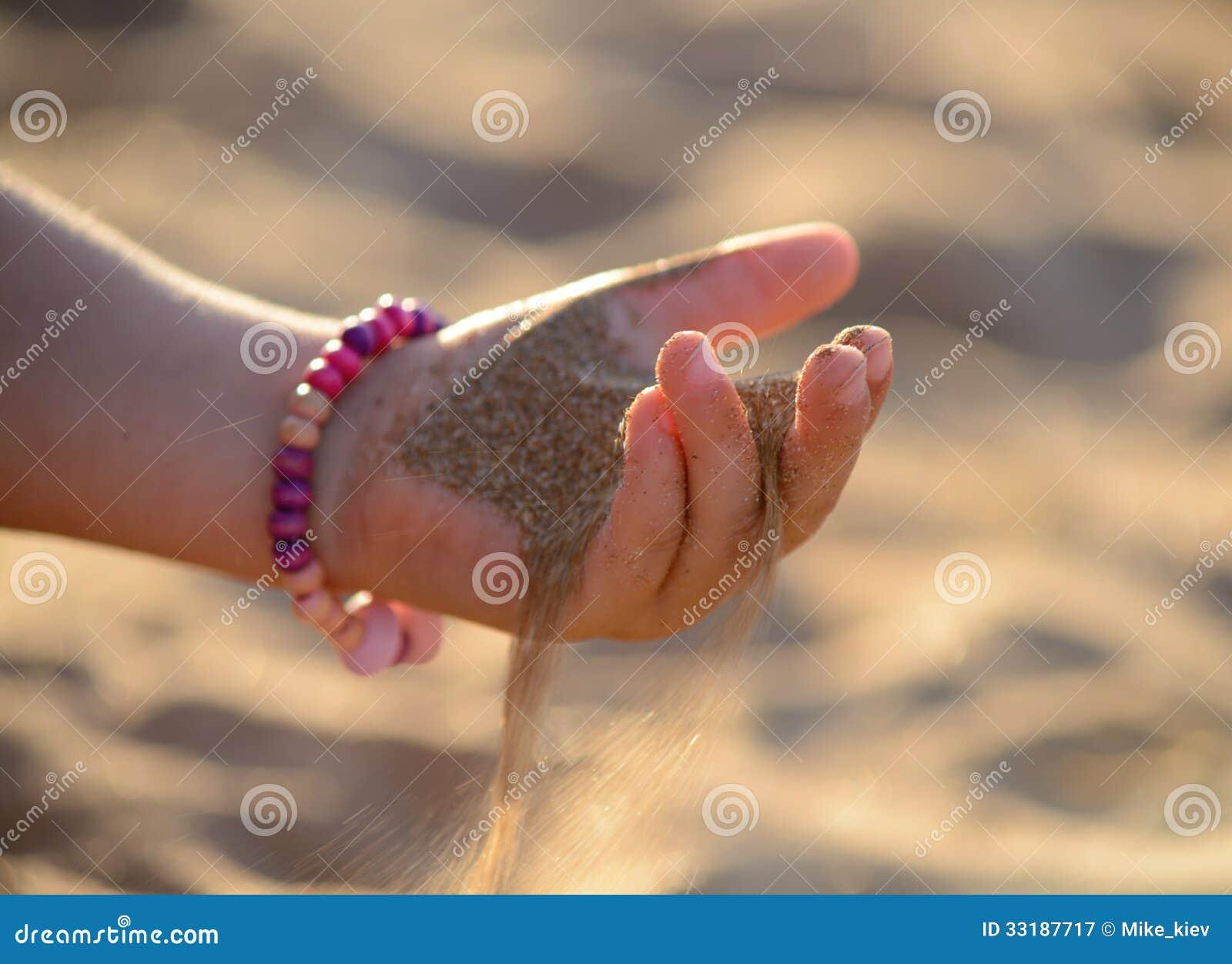 A areia derrama fora da mão da criança