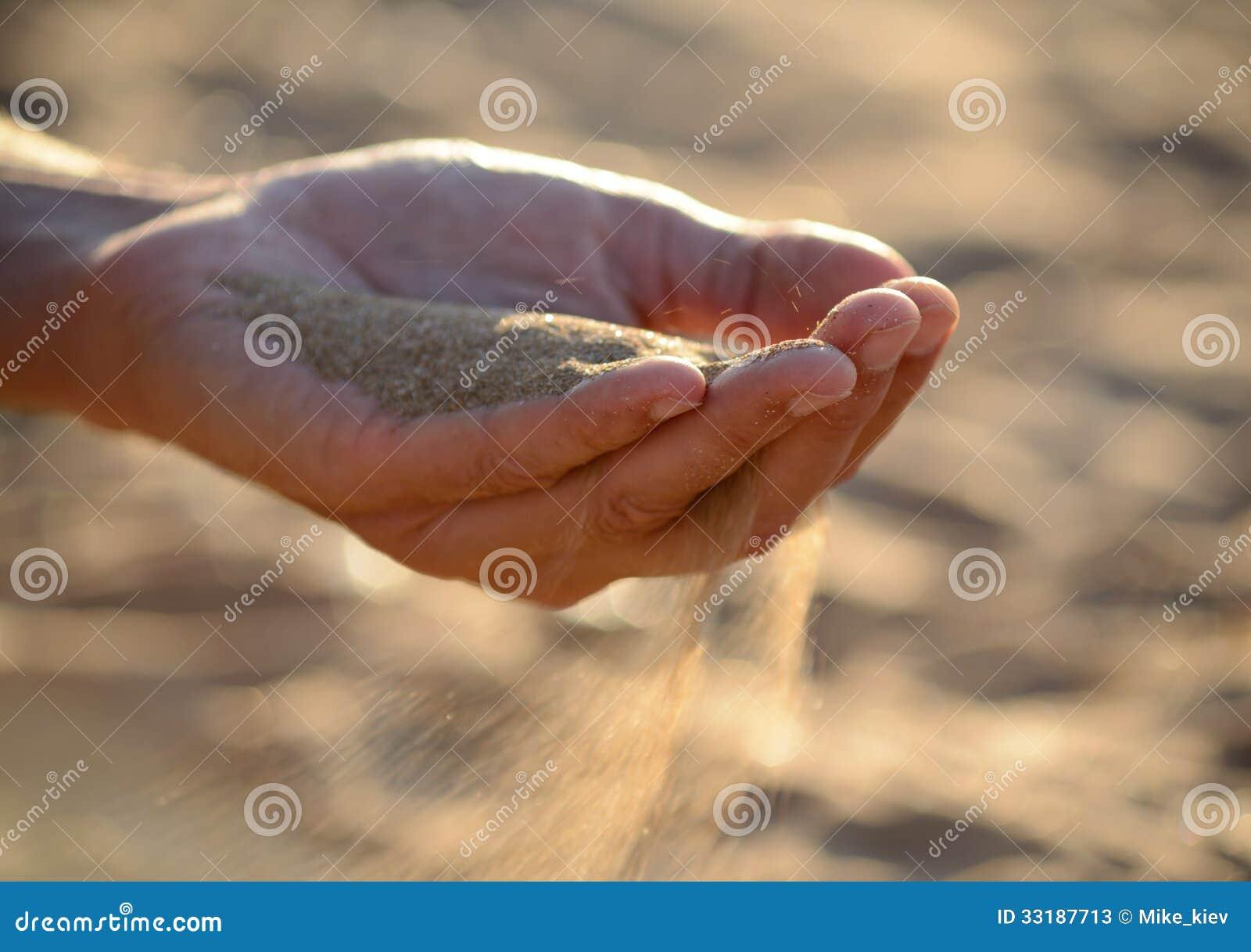 A areia derrama fora das mãos