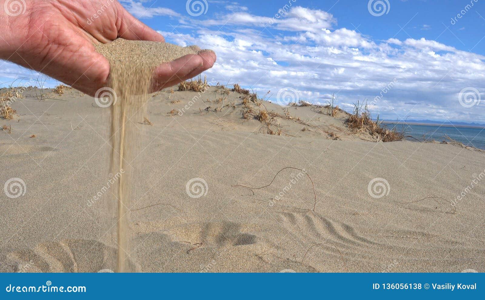 Areia nas mãos do conceito do deserto