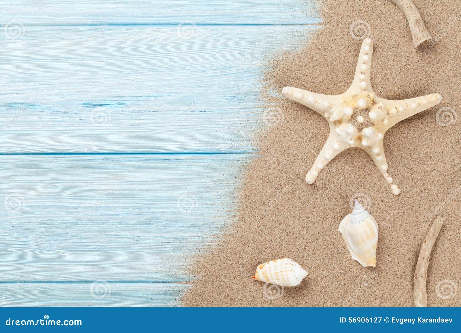Arena de mar con las estrellas de mar y las cáscaras en la madera