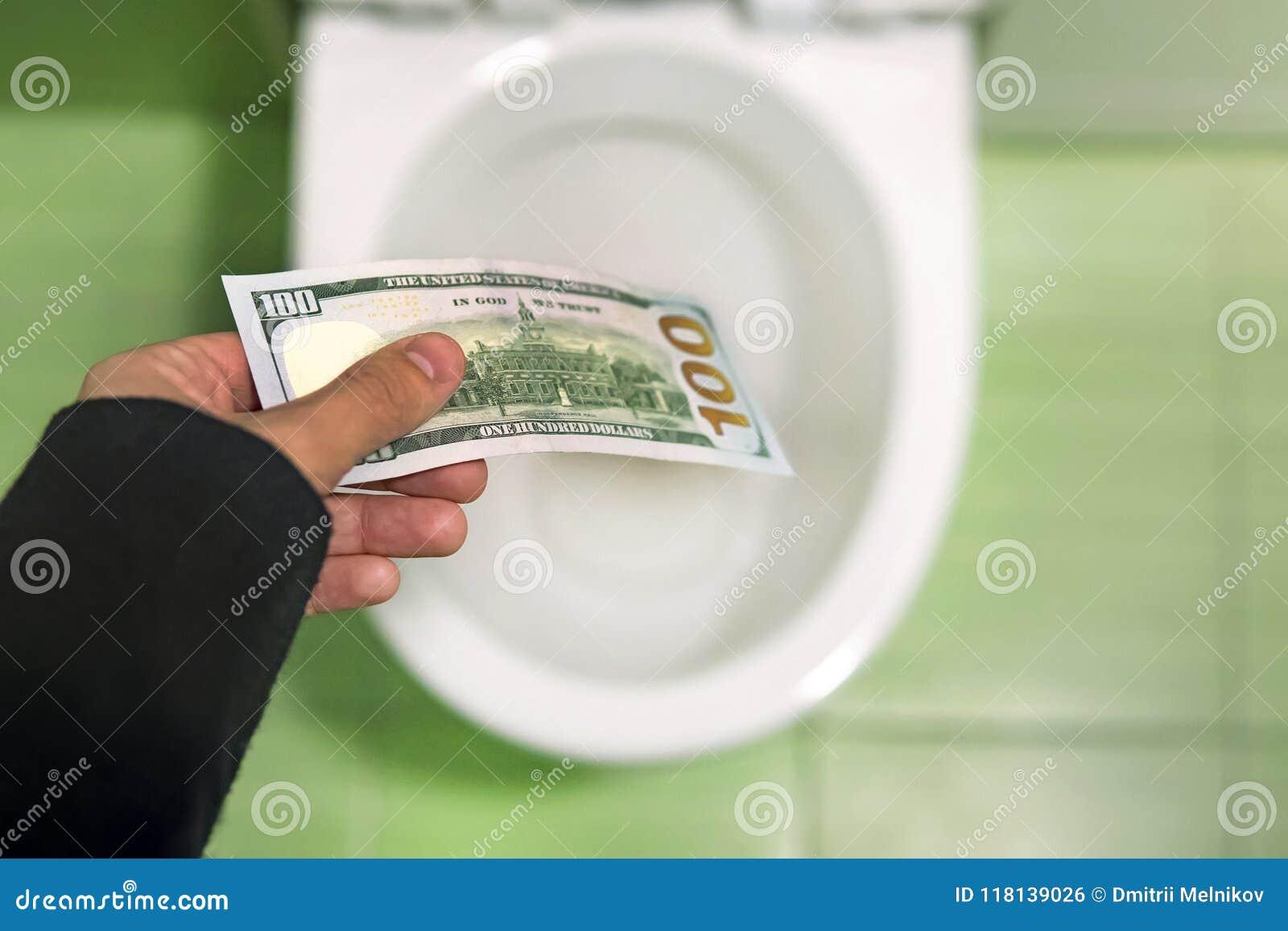 Argent affleurant en bas de la toilette, billets d un dollar de jets dans la toilette, concept de perte, fin, foyer sélectif