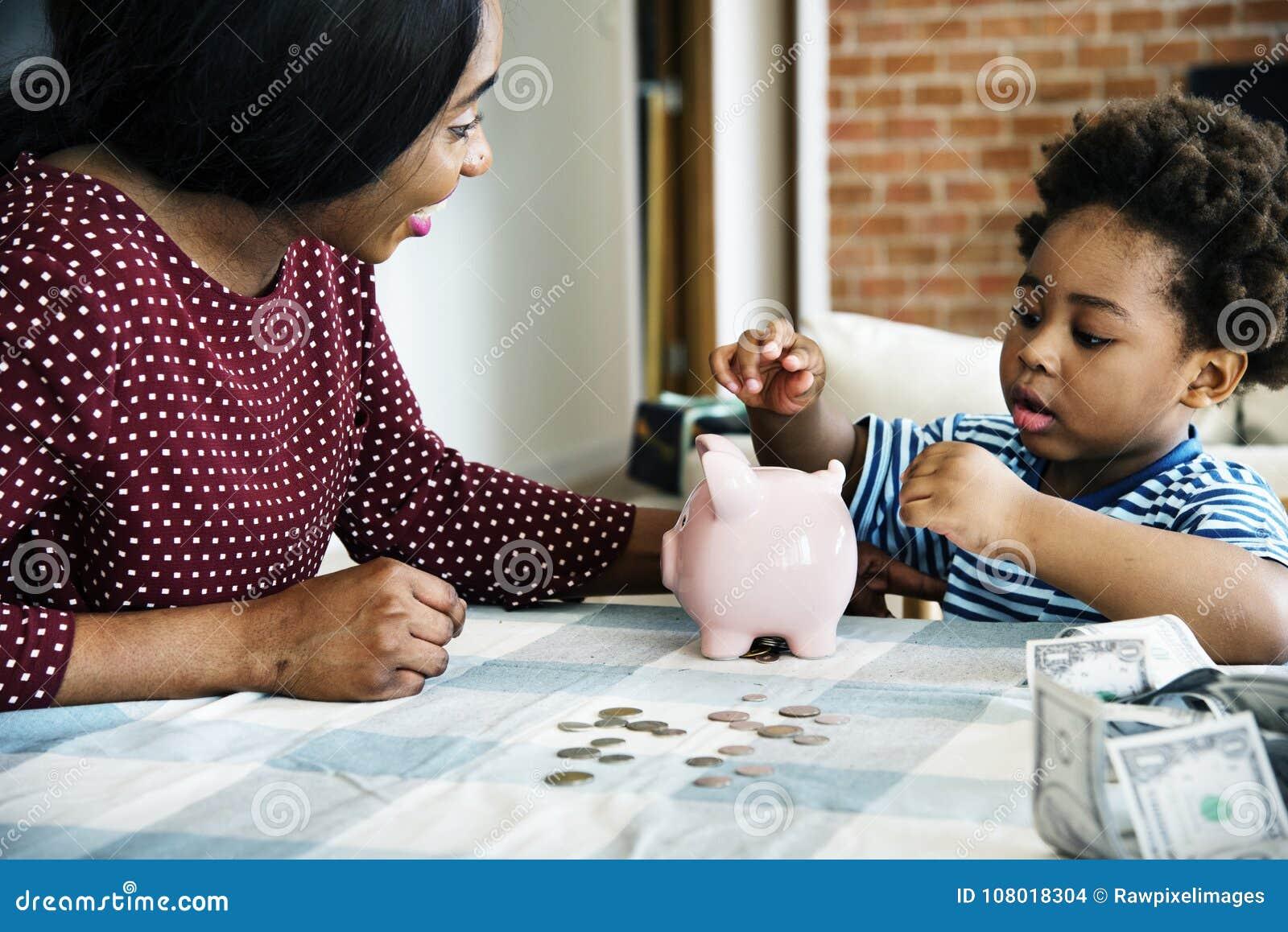 Argent d économie de maman et de fils vers la tirelire