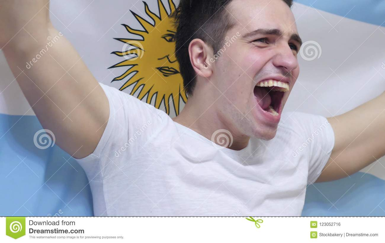 Argentinian Young Man celebrating while holding the Flag of Argentina in Slow Motion