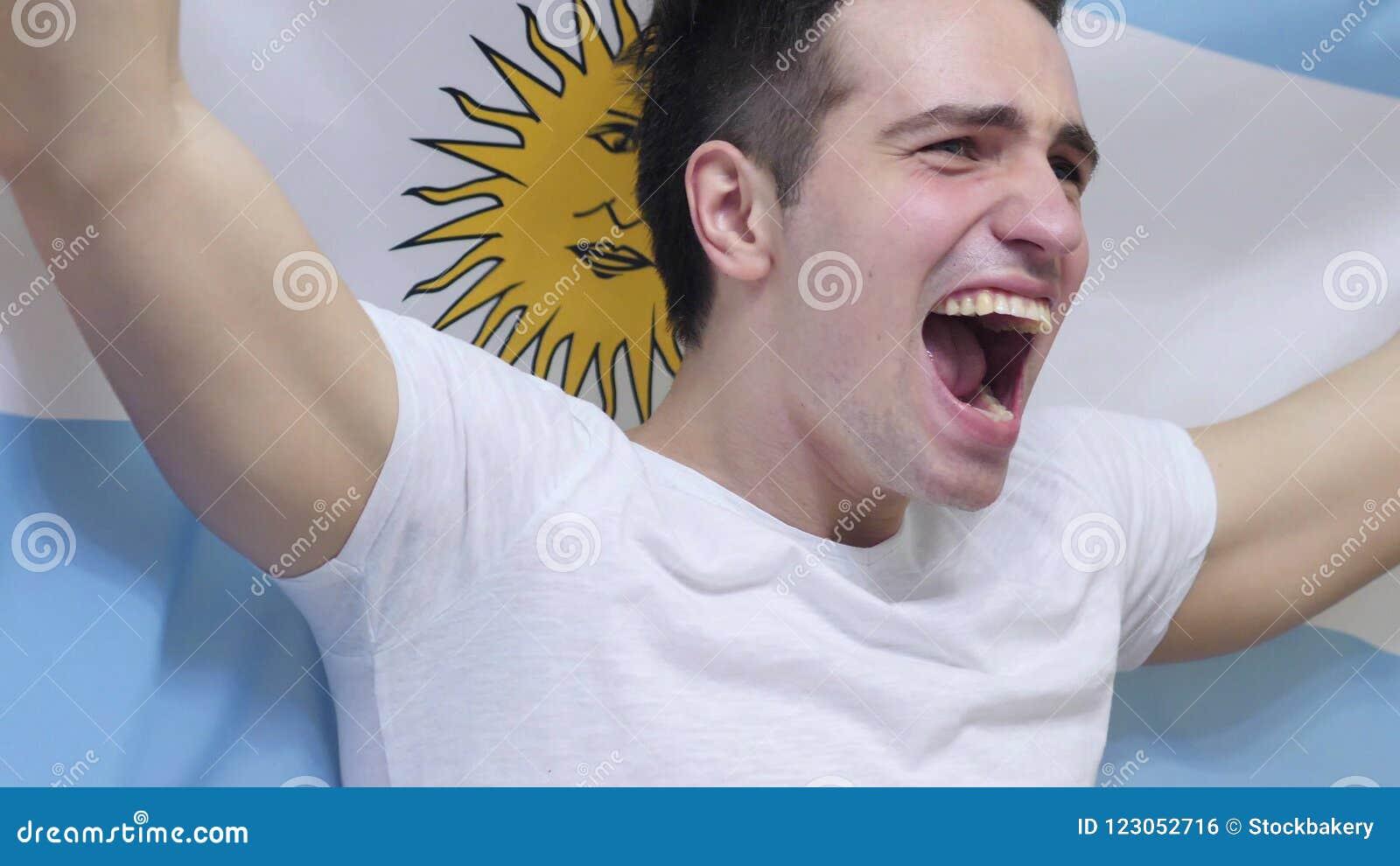 Argentyńska młody człowiek odświętność podczas gdy trzymający flaga Argentyna w zwolnionym tempie