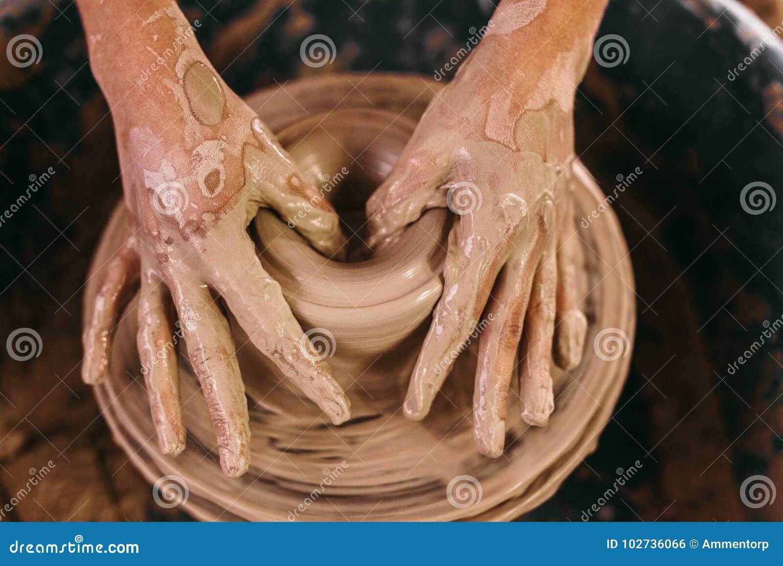 Argila moldando do oleiro na roda da cerâmica