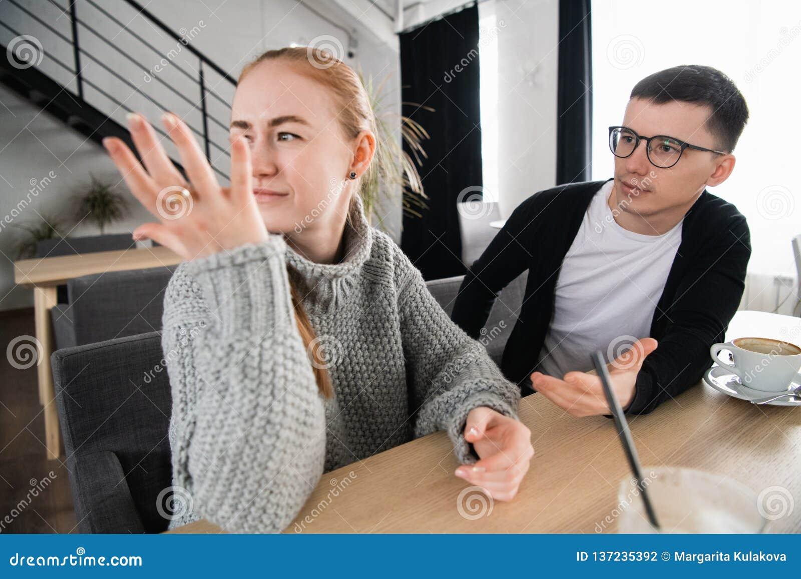 Argumentera par som ifrån varandra hemma sitter Ung ledsen kvinna som tänker om försoning med pojkvännen