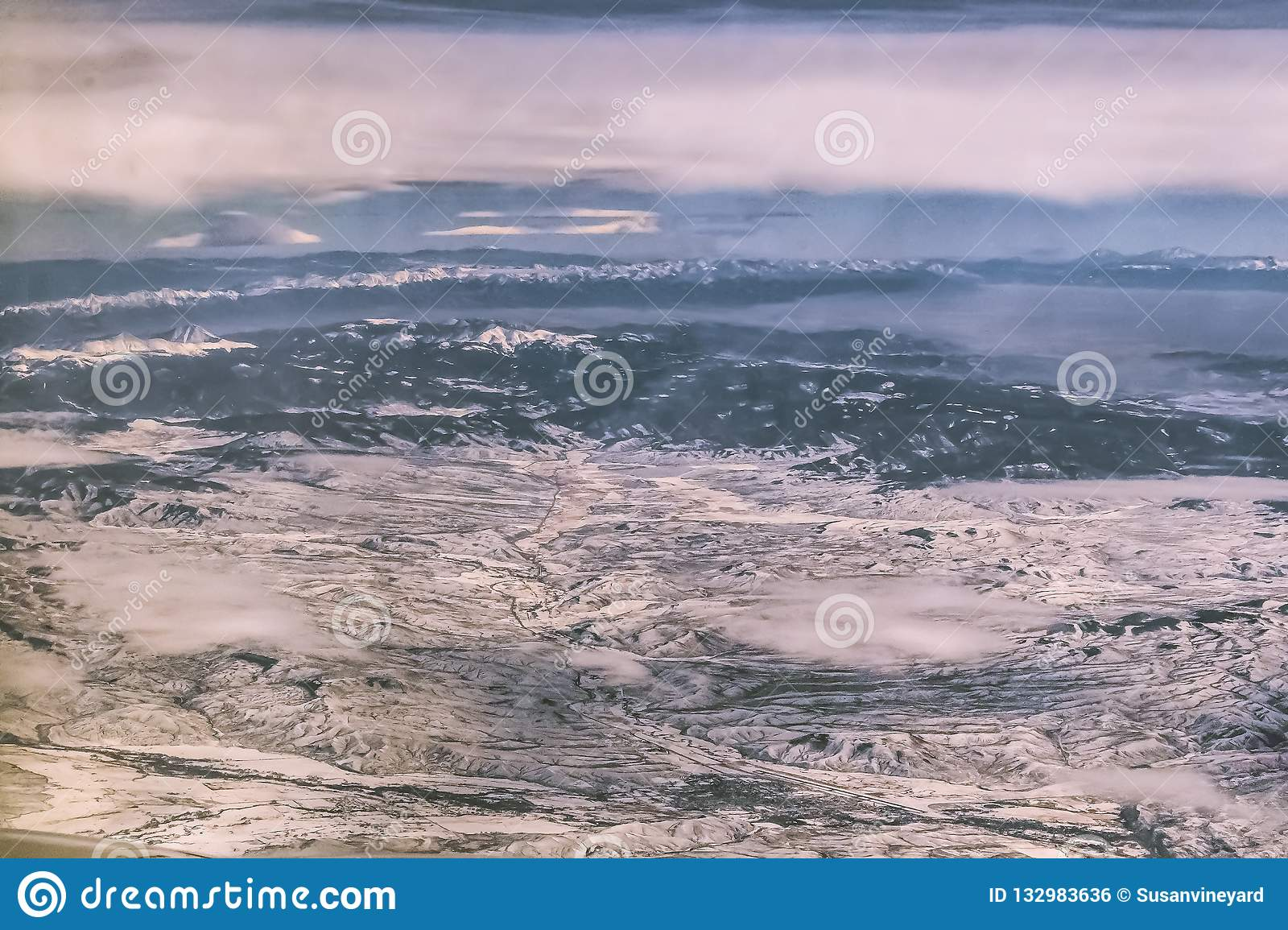 Arial view of snow covered terrain with mountains in the distance and a few low clouds over a river and a town and a highway somew