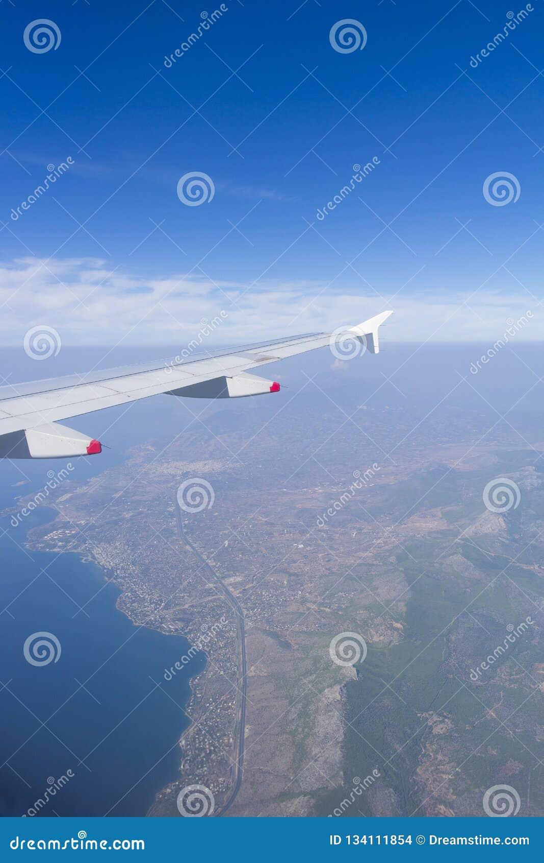 Arielmening van een vliegtuig het vliegen, prachtig landschap, bergen onderaan met blauwe hemel en wolken