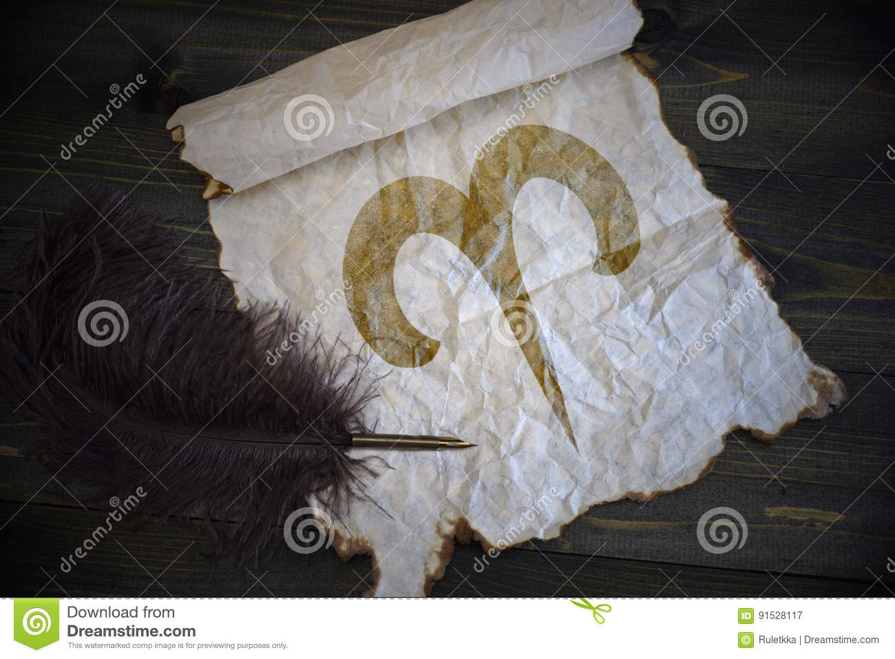 Aries sign of the zodiac on vintage paper with old pen on the wooden desk