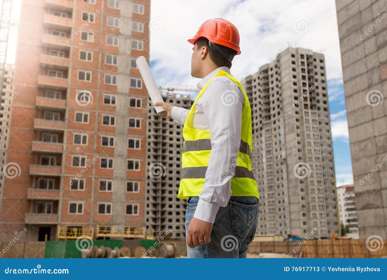 Arkitekt i hardhat som pekar med rullande ritningar på byggnad