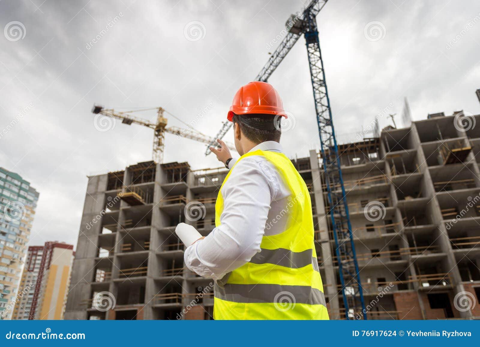 Arkitekt i hardhat som pekar på byggnad under konstruktion