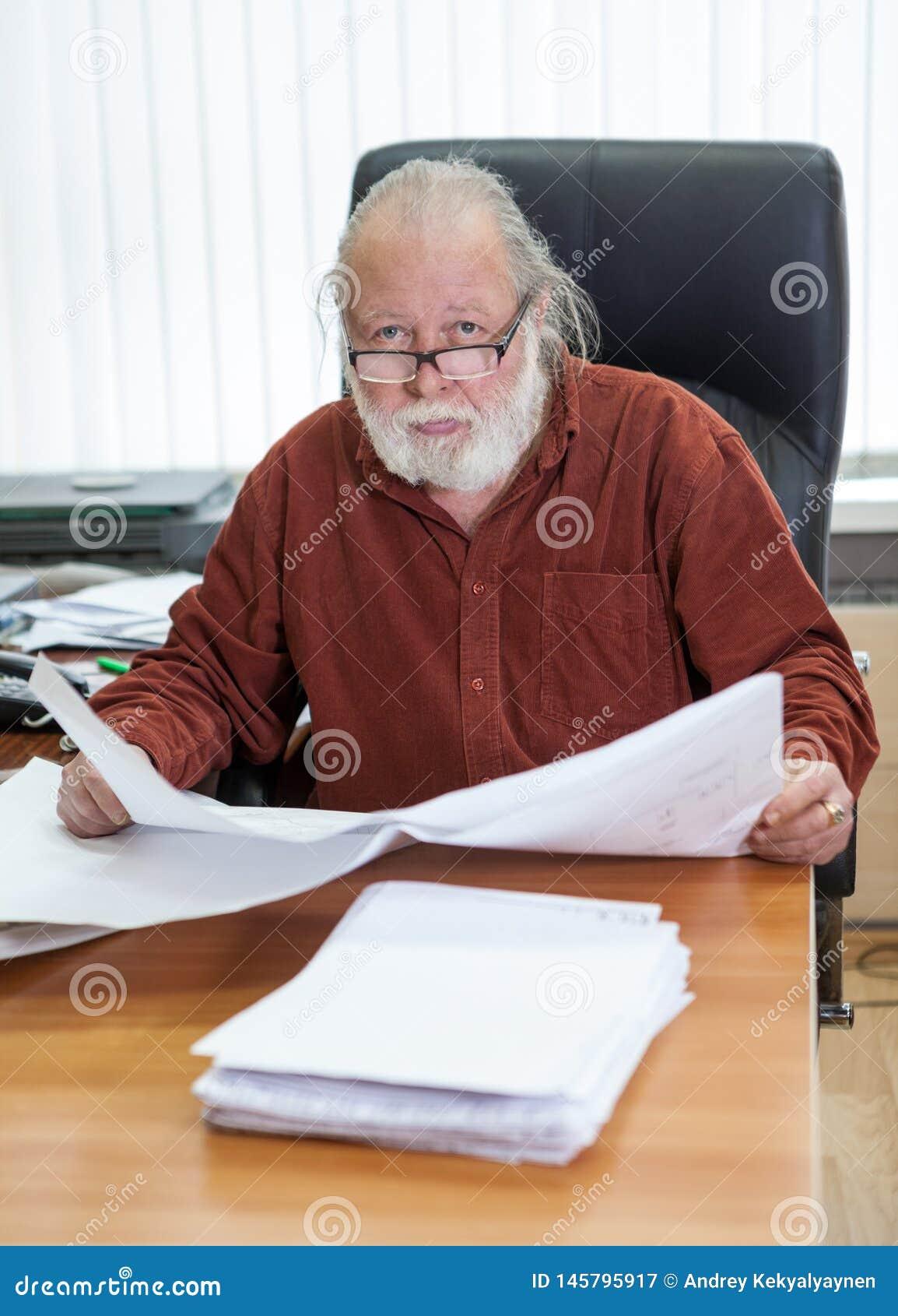 Arkitekten med ritningar på hans jobb, åldrades den Caucasian arbetaren för den vita kragen för mannen