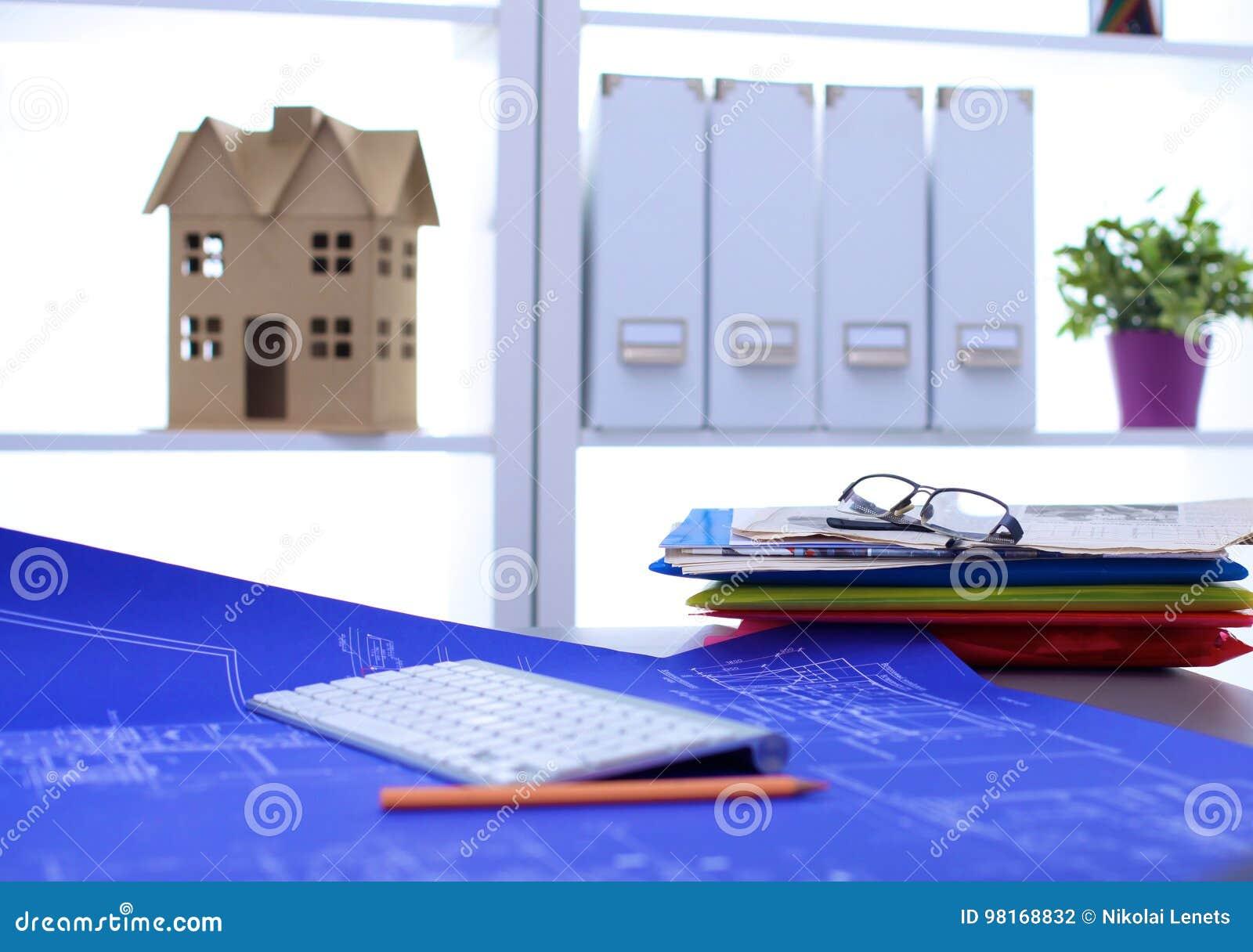 Arkitektoniska ritningar och ritningrullar och instrument för en teckning på worktablen