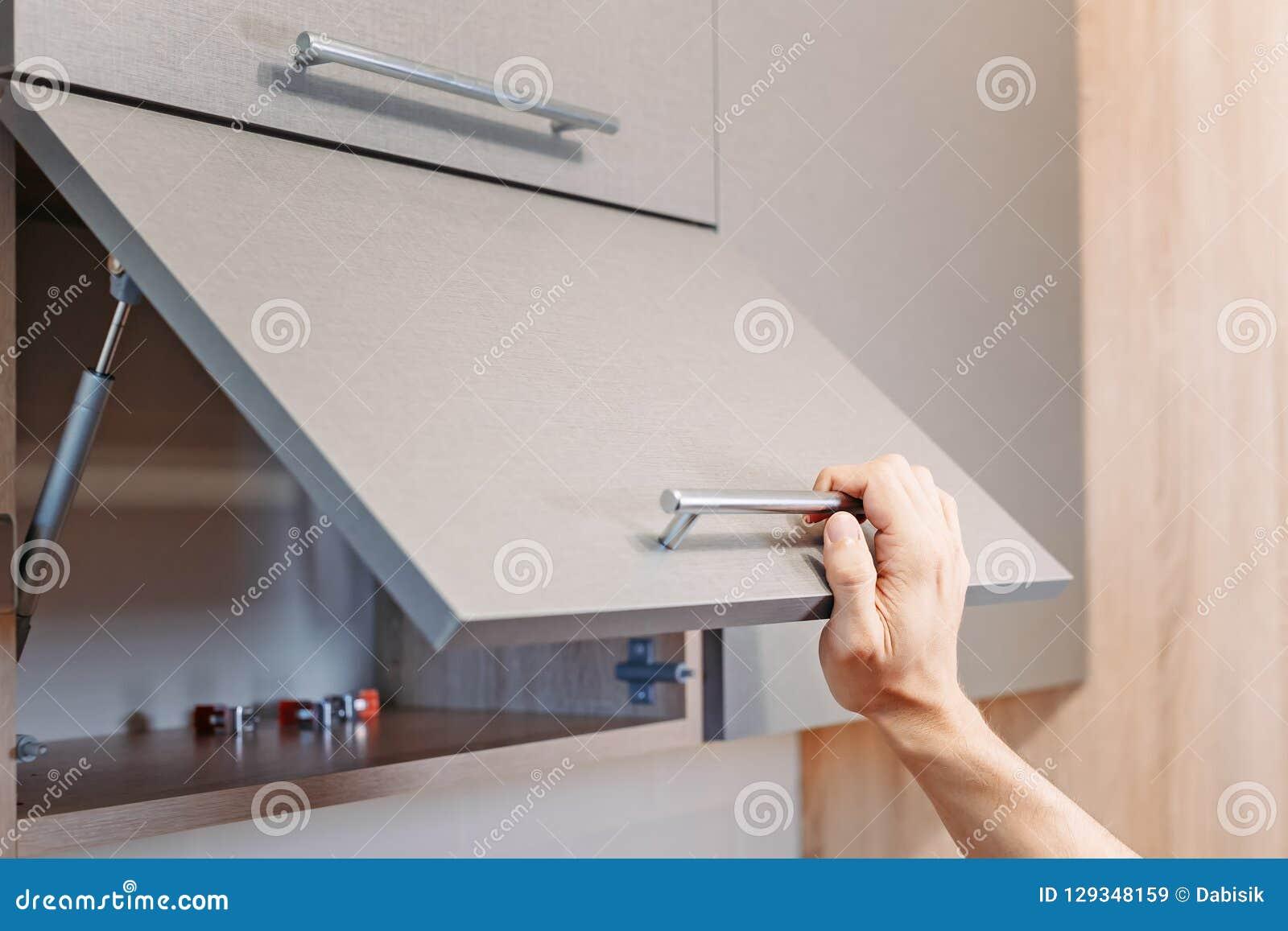 Armadietto aperto della cucina della mano dell uomo con la maniglia