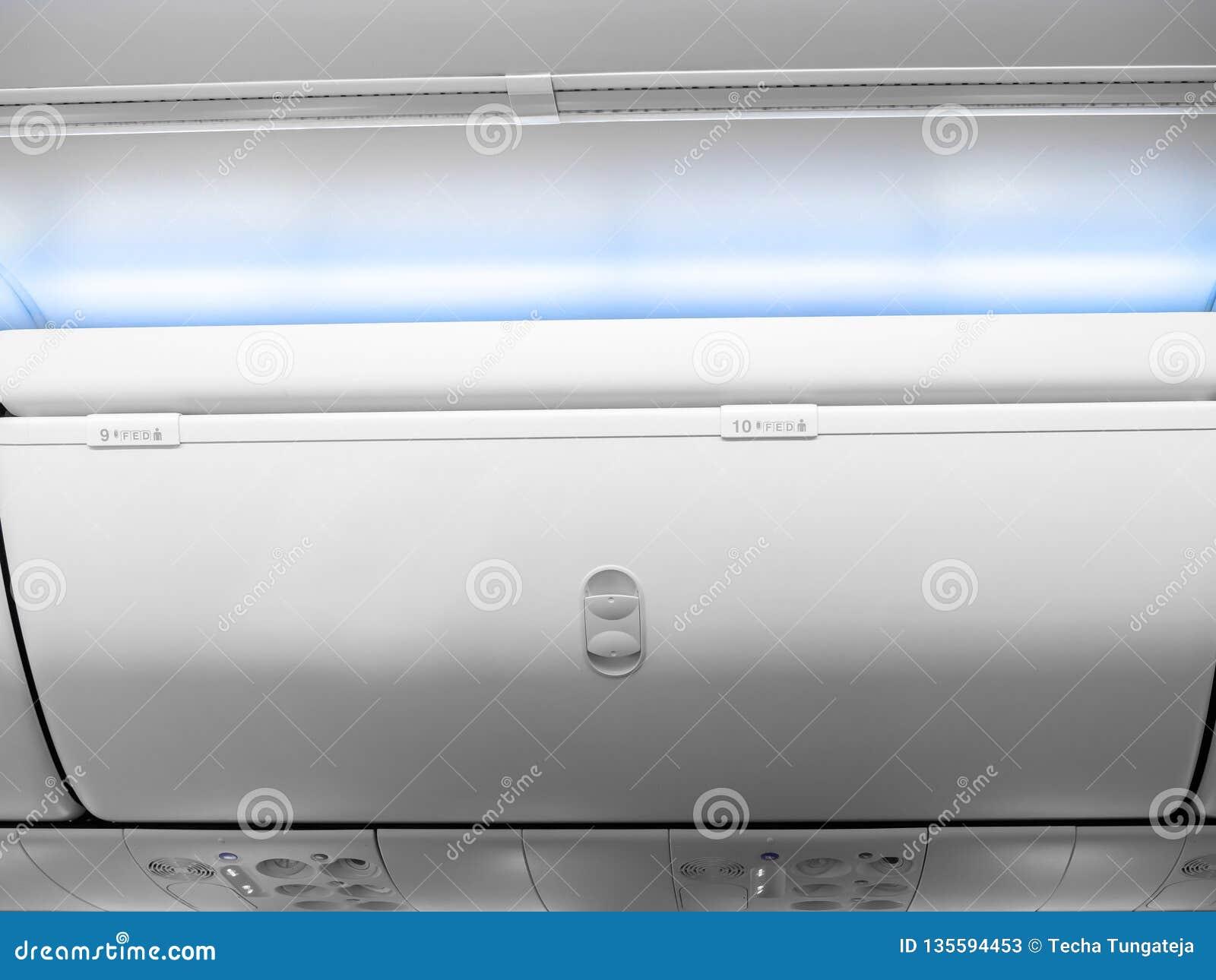 Armadio di bagagli bianco numeri 9 e 10 con luce blu nella classe economica della cabina in aeroplano commerciale