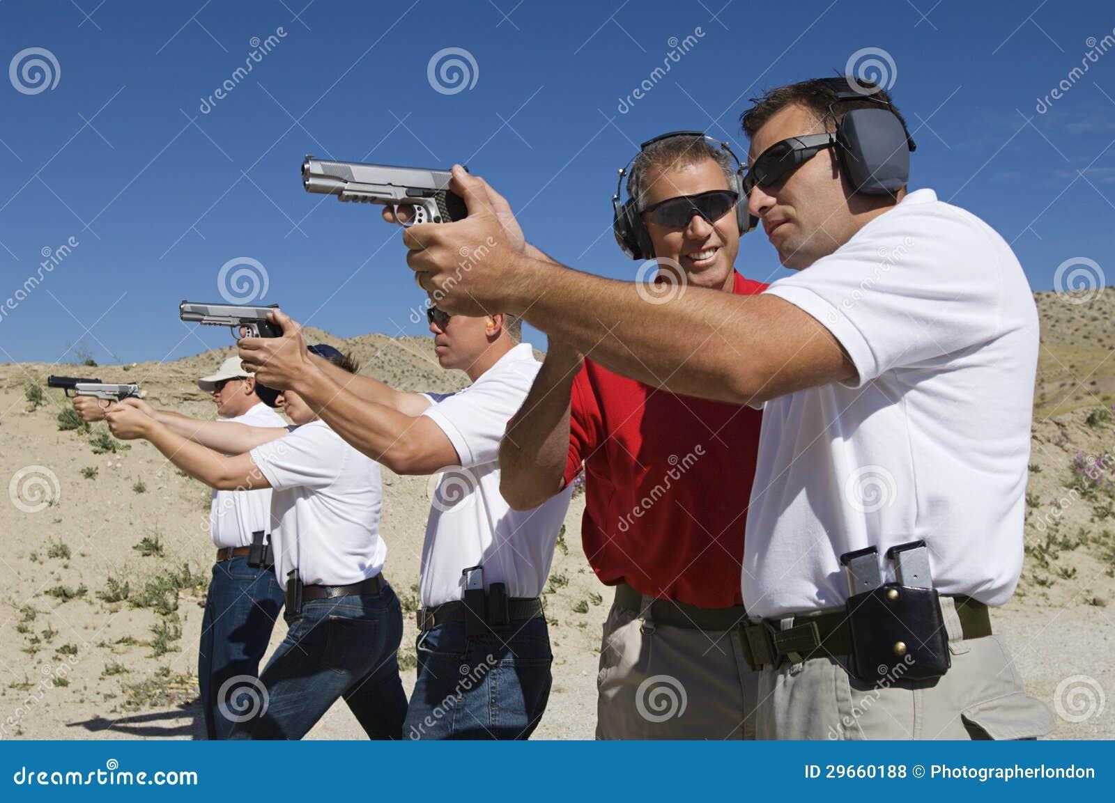Armas de la mano de Assisting Officers With del instructor en la gama de leña