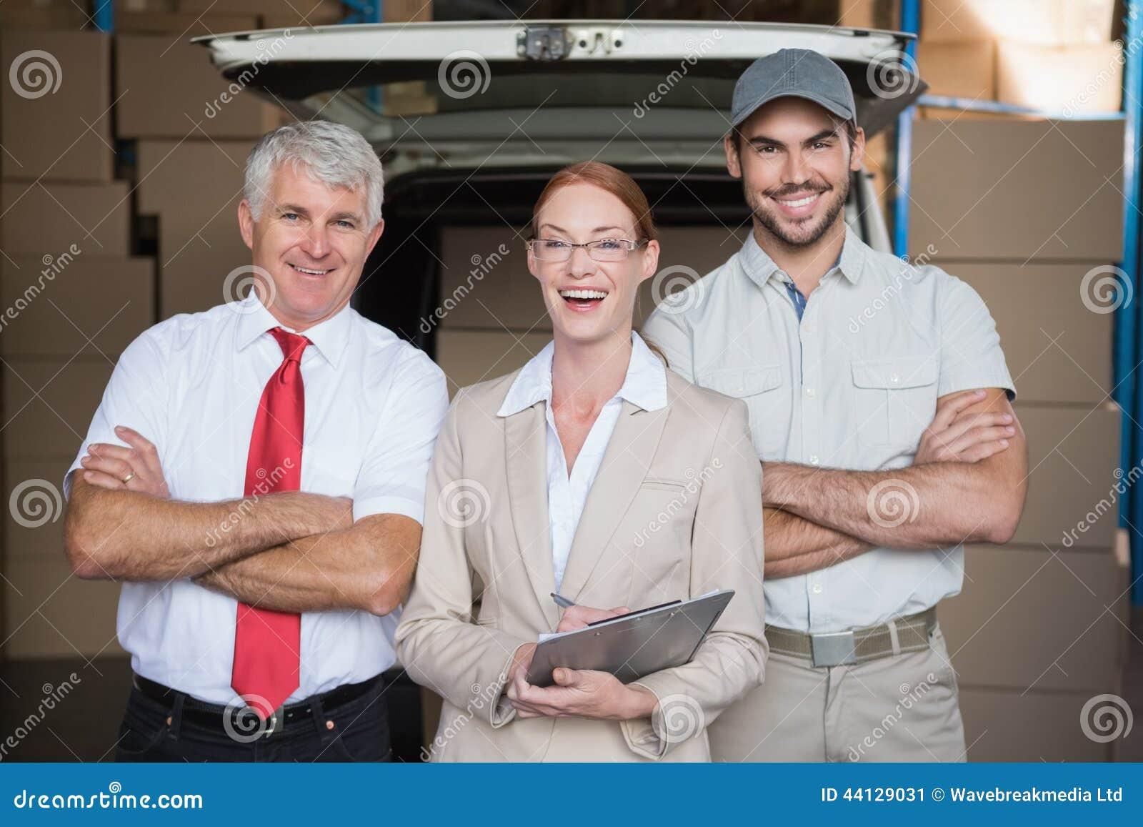 Armazene os gerentes e o motorista da entrega que sorriem na câmera