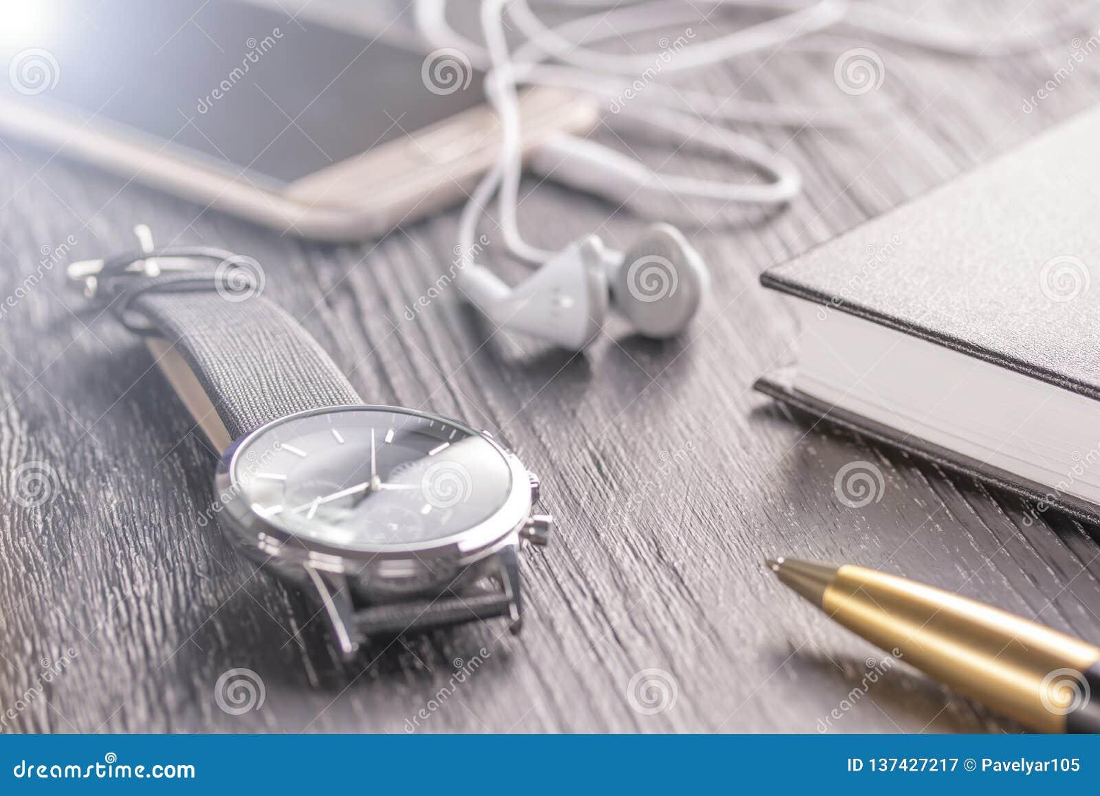 Armbanduhr, Handy mit Kopfhörern und ein Notizblock mit einem Stift auf einem alten dunklen Bürodesktop