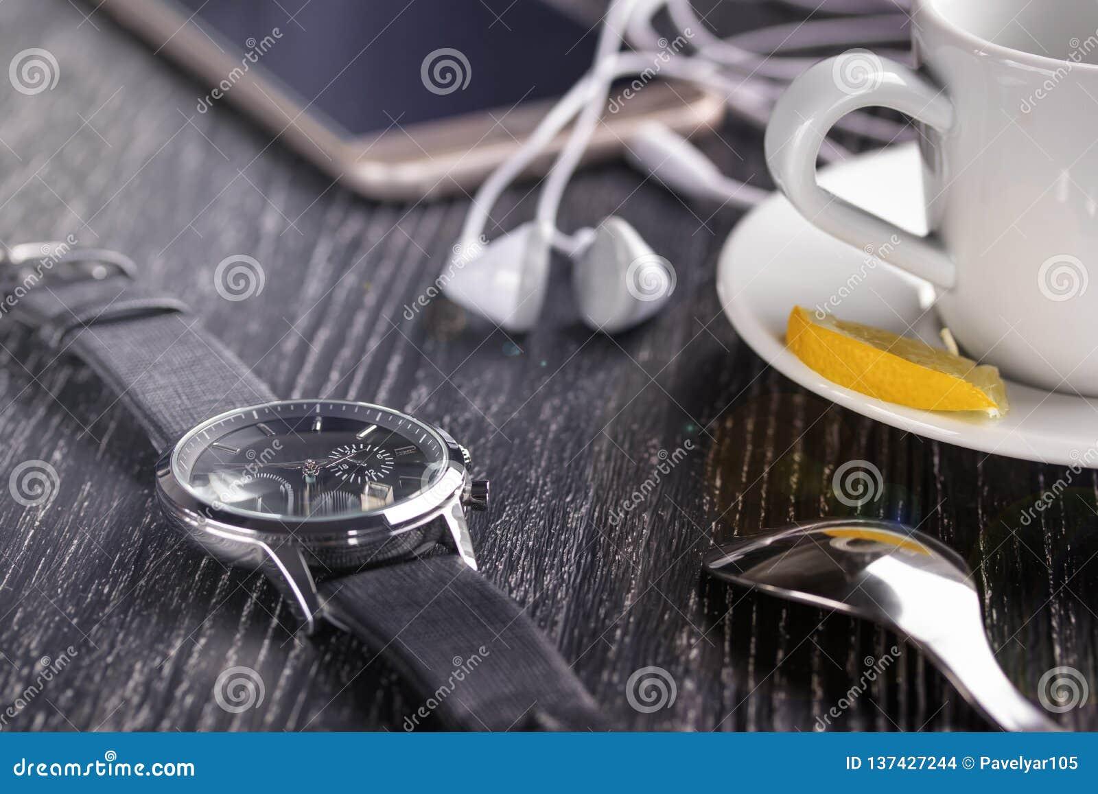 Armbanduhr und Handy mit Kopfhörern und einem Tasse Kaffee auf einem dunklen Holztisch