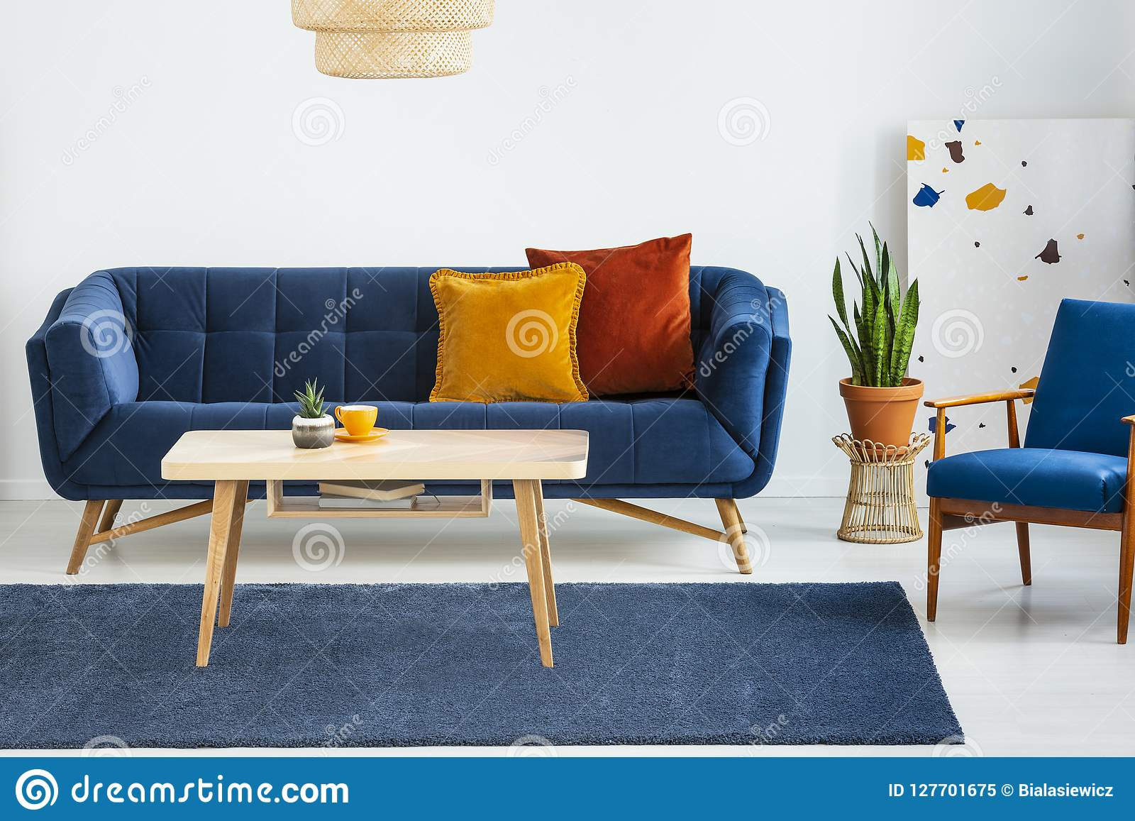 Armchair Next To Blue Sofa With Cushions And Wooden Table In Flat