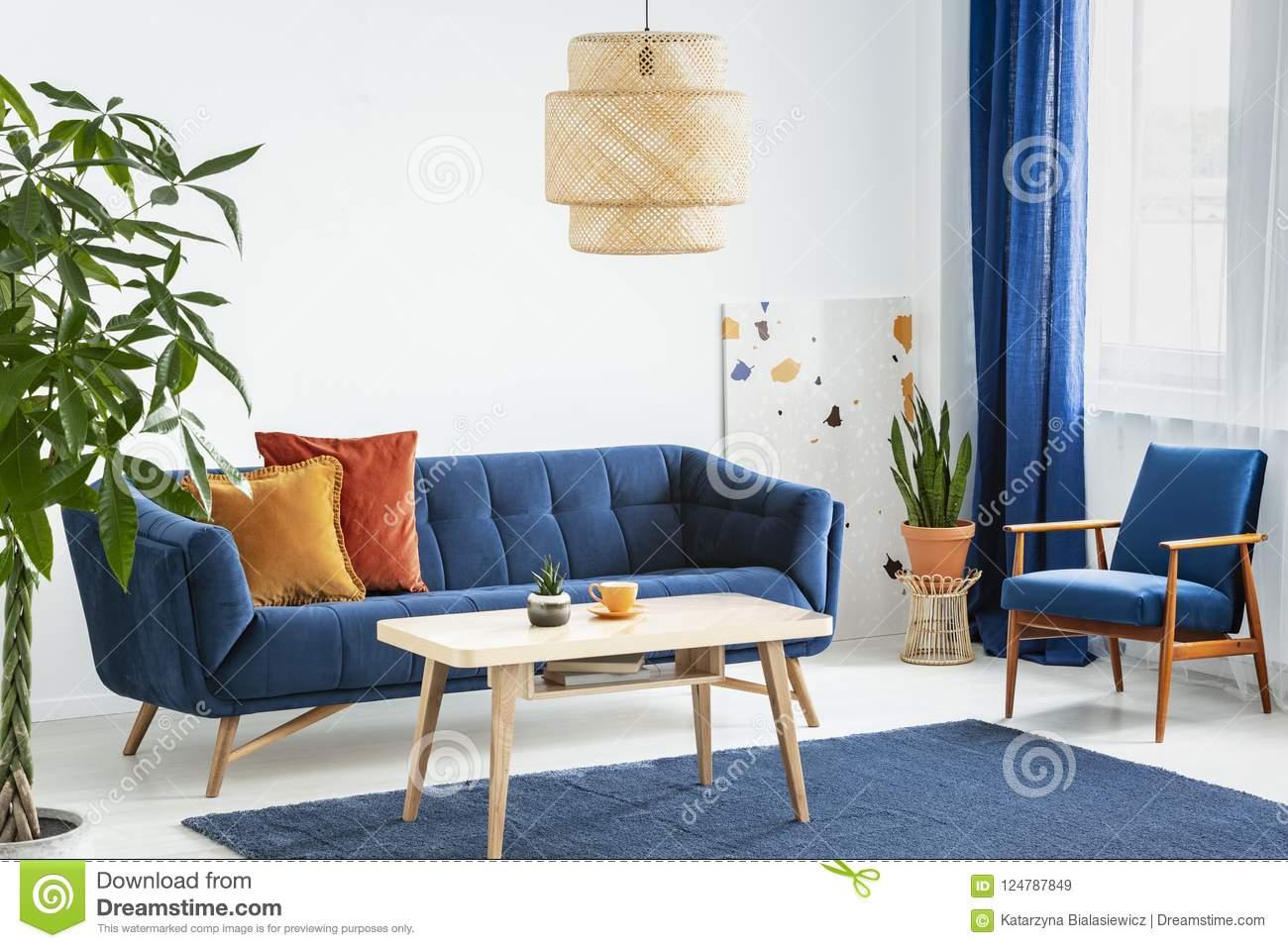Armchair And Sofa In Blue And Orange Living Room Interior With Lamp