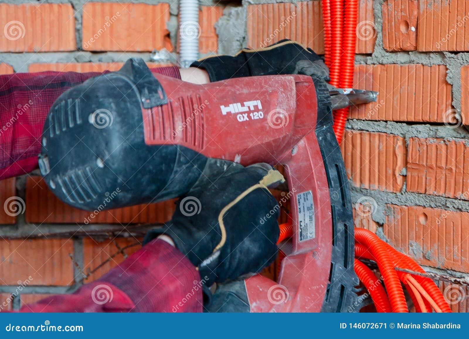 Arme à feu du clou de Hilti conduisant un clou dans un mur