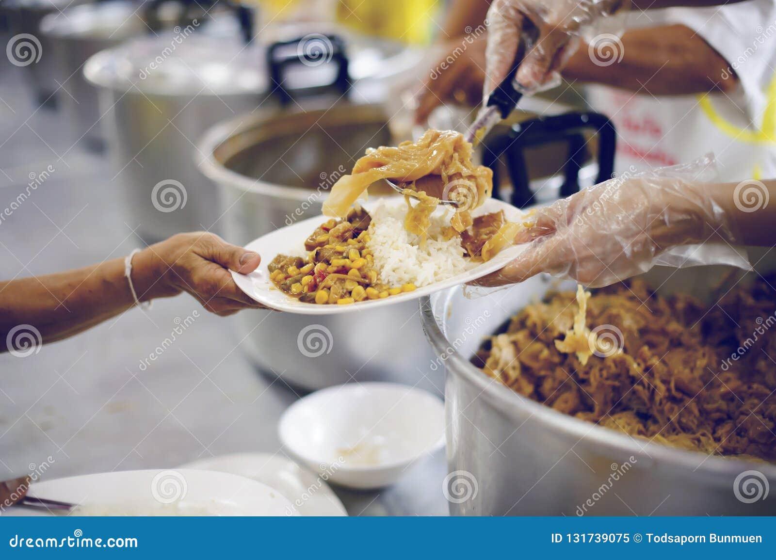 Arme Leute empfangen gespendete Nahrung von den Spendern, demonstrieren das gegenseitige Teilen in der heutigen Gesellschaft: das