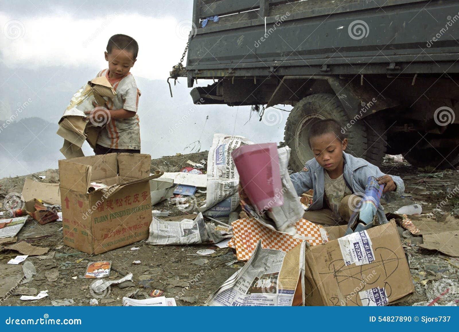 Arme philippinische Jungen, die altes Papier auf Müllgrube erfassen