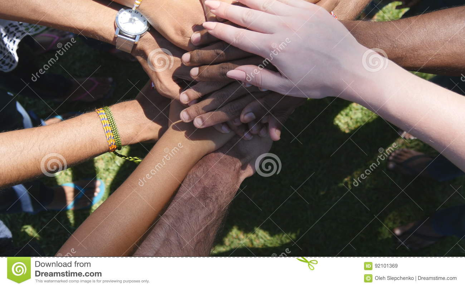 Armen springer allra och färger som tillsammans en och en staplas i enhet och teamwork och lyfts därefter Många blandras- händer