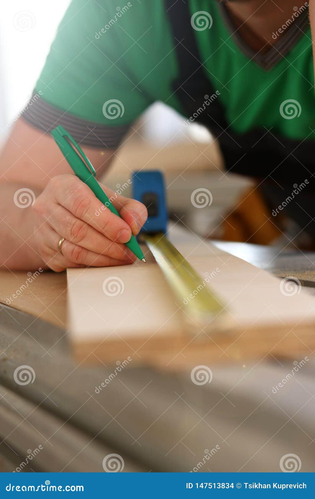 Armi del lavoratore che misurano il primo piano di legno della barra