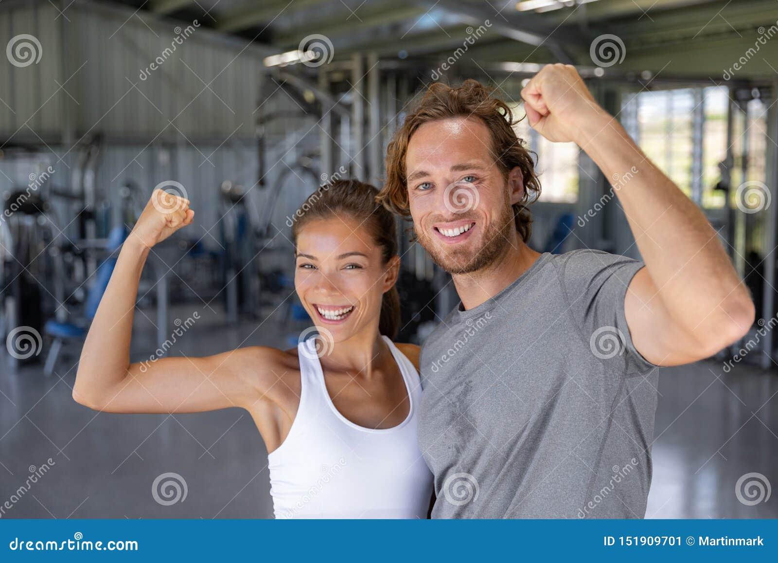 Armi forti di flessione felici delle coppie adatte di potere che ostentano addestramento di successo alla palestra di forma fisic