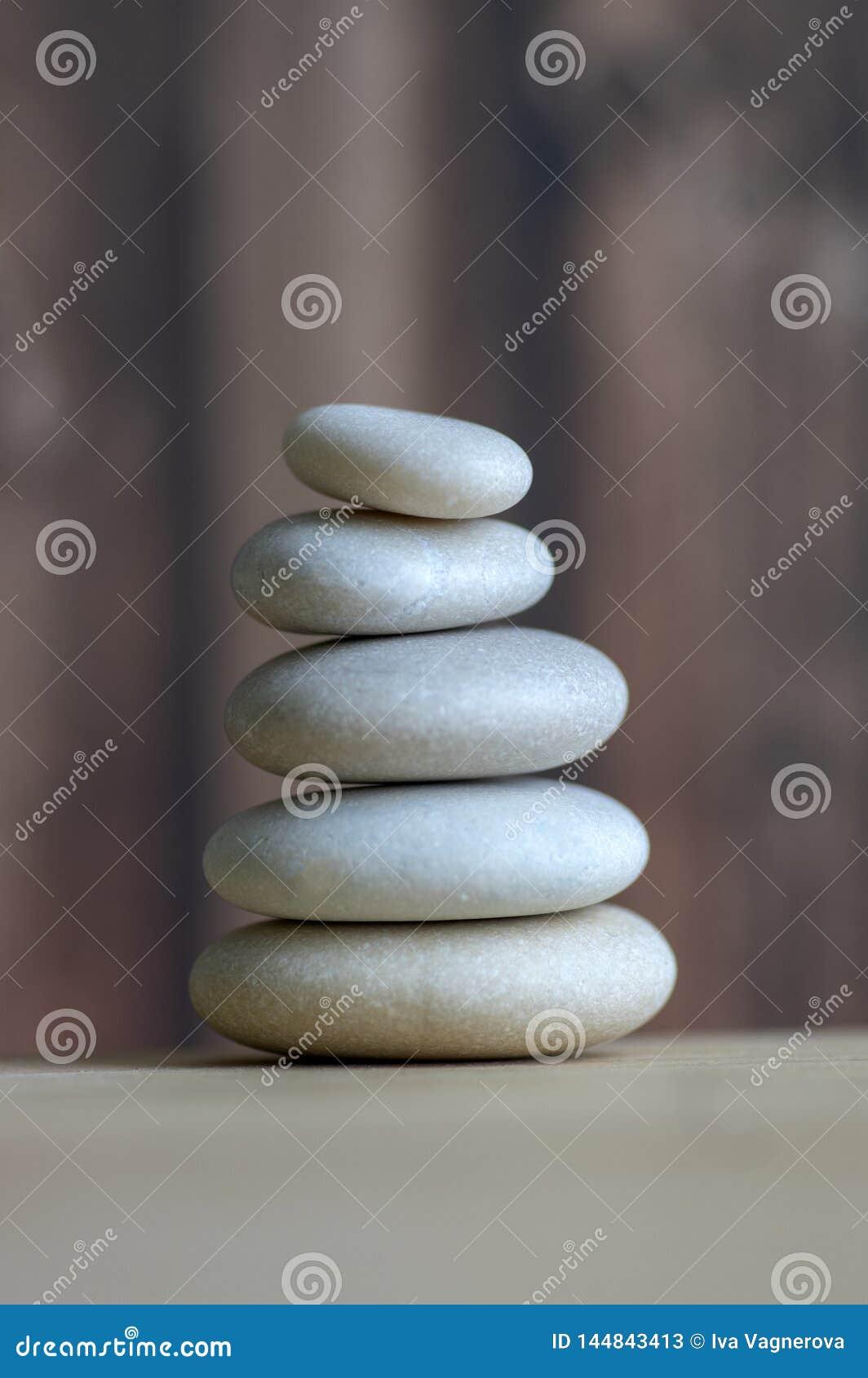 Armonia ed equilibrio, cairn, pietre semplici di equilibrio su fondo bianco, scultura di zen della roccia, cinque ciottoli bianch