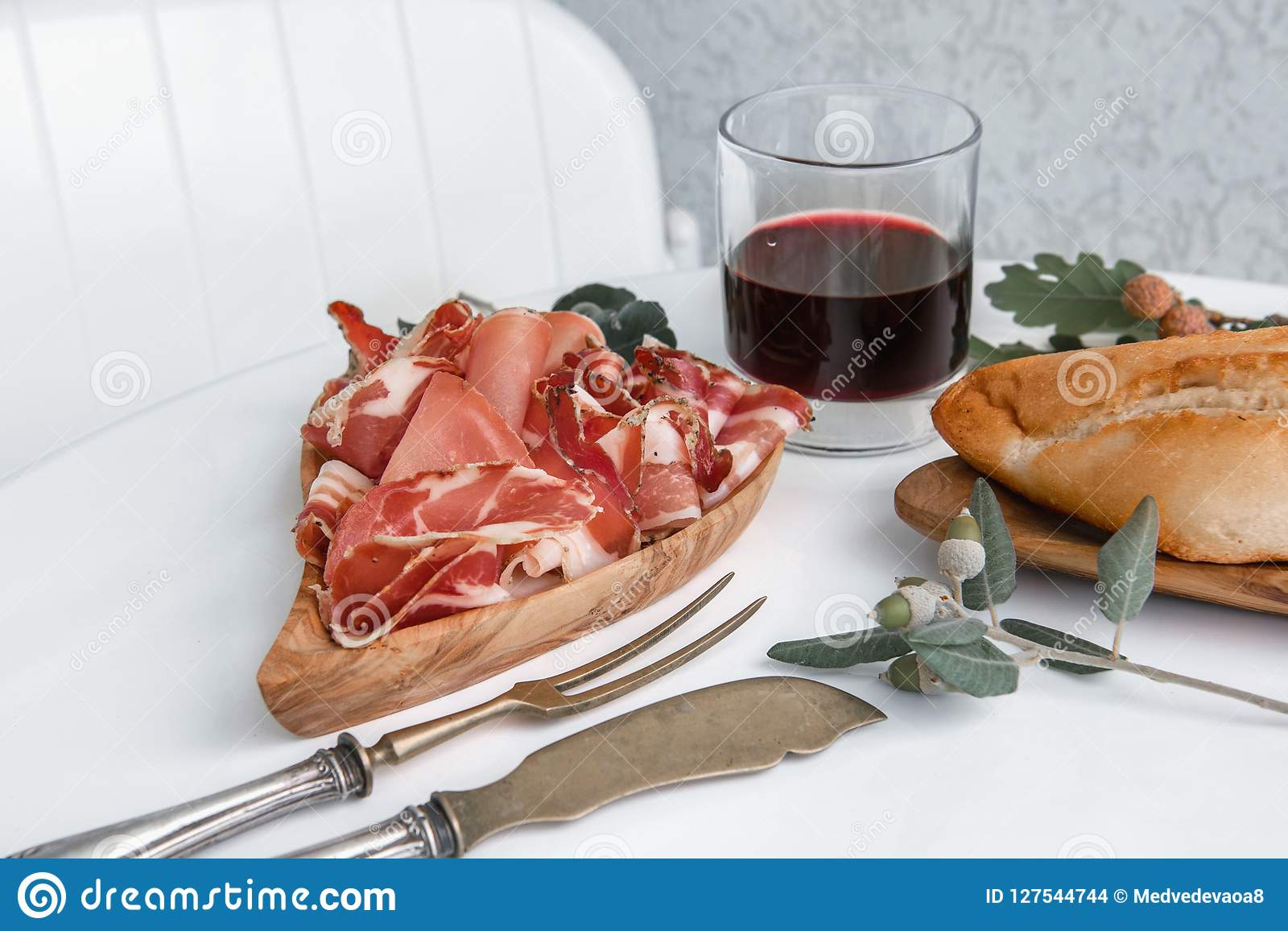 The aroma of ham and spices, thinly sliced on a white table with bread and antique Cutlery