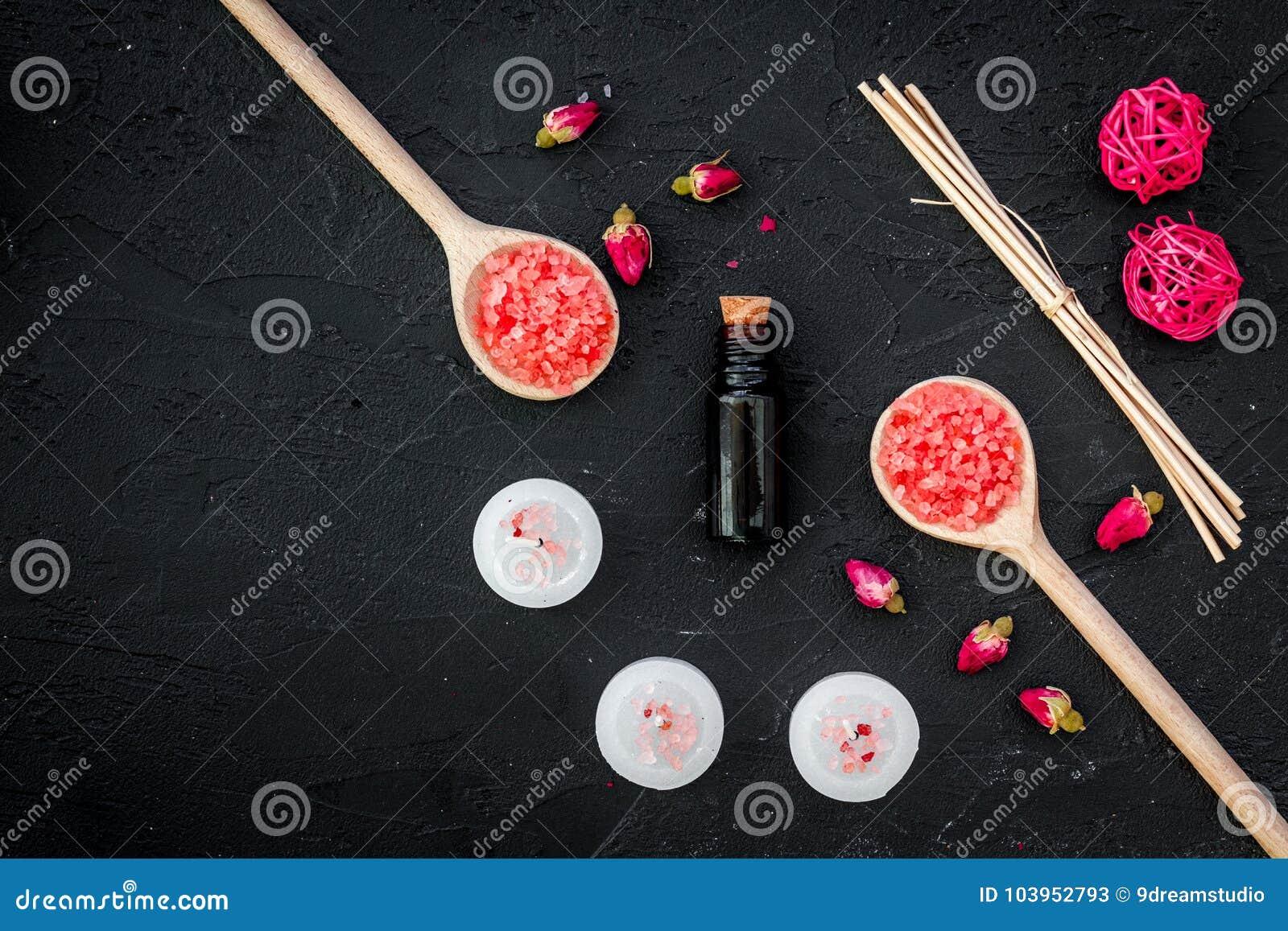 Aromatherapy voor ontspant concept Nam knoppen, kuuroordzout, kaarsen en olie op zwarte hoogste mening als achtergrond copyspace