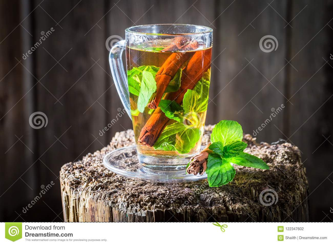 Aromatic and fresh tea with cinnamon bark and green leaves