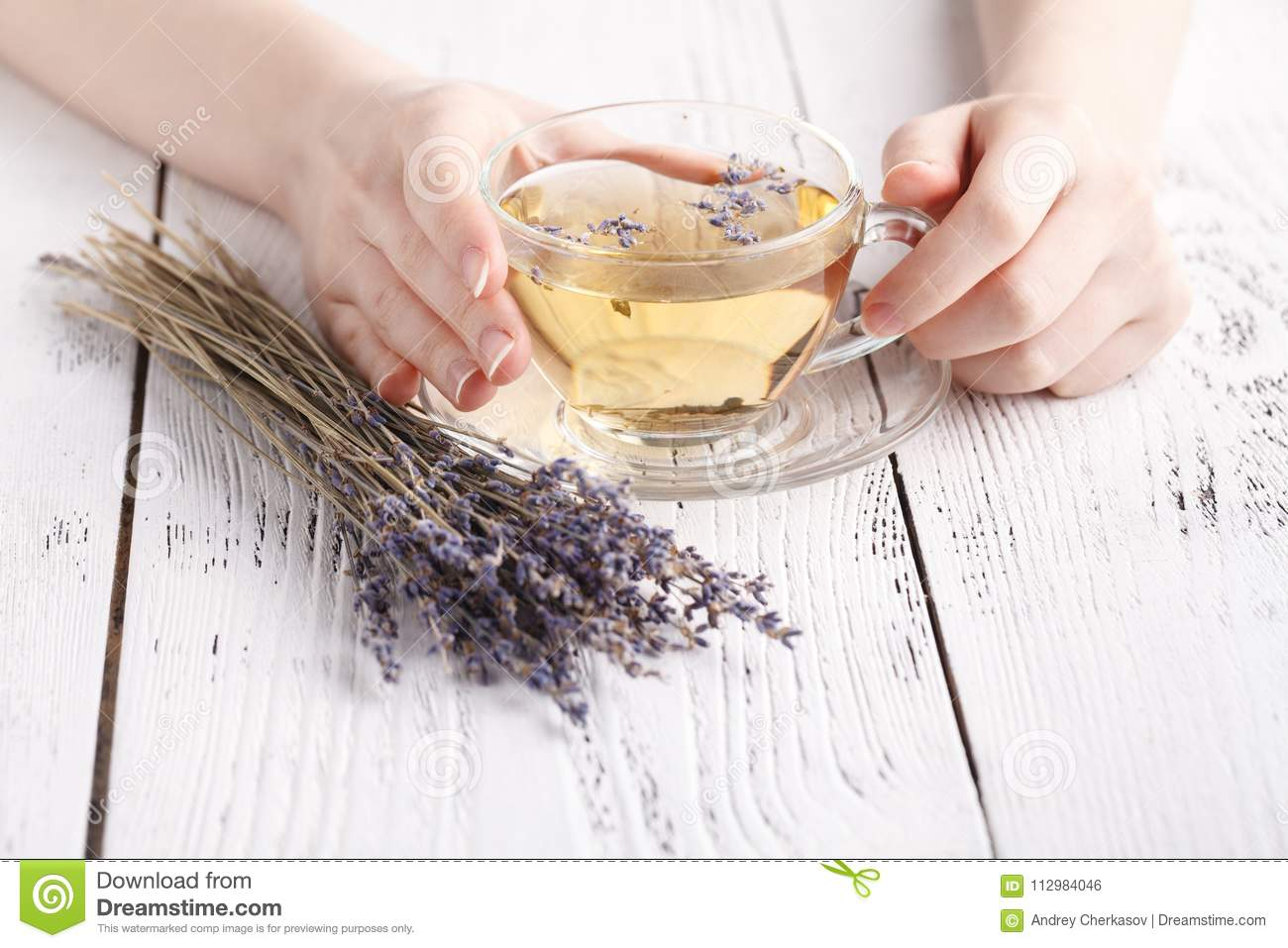 Aromatic herbal tea in glass cup holding female hands