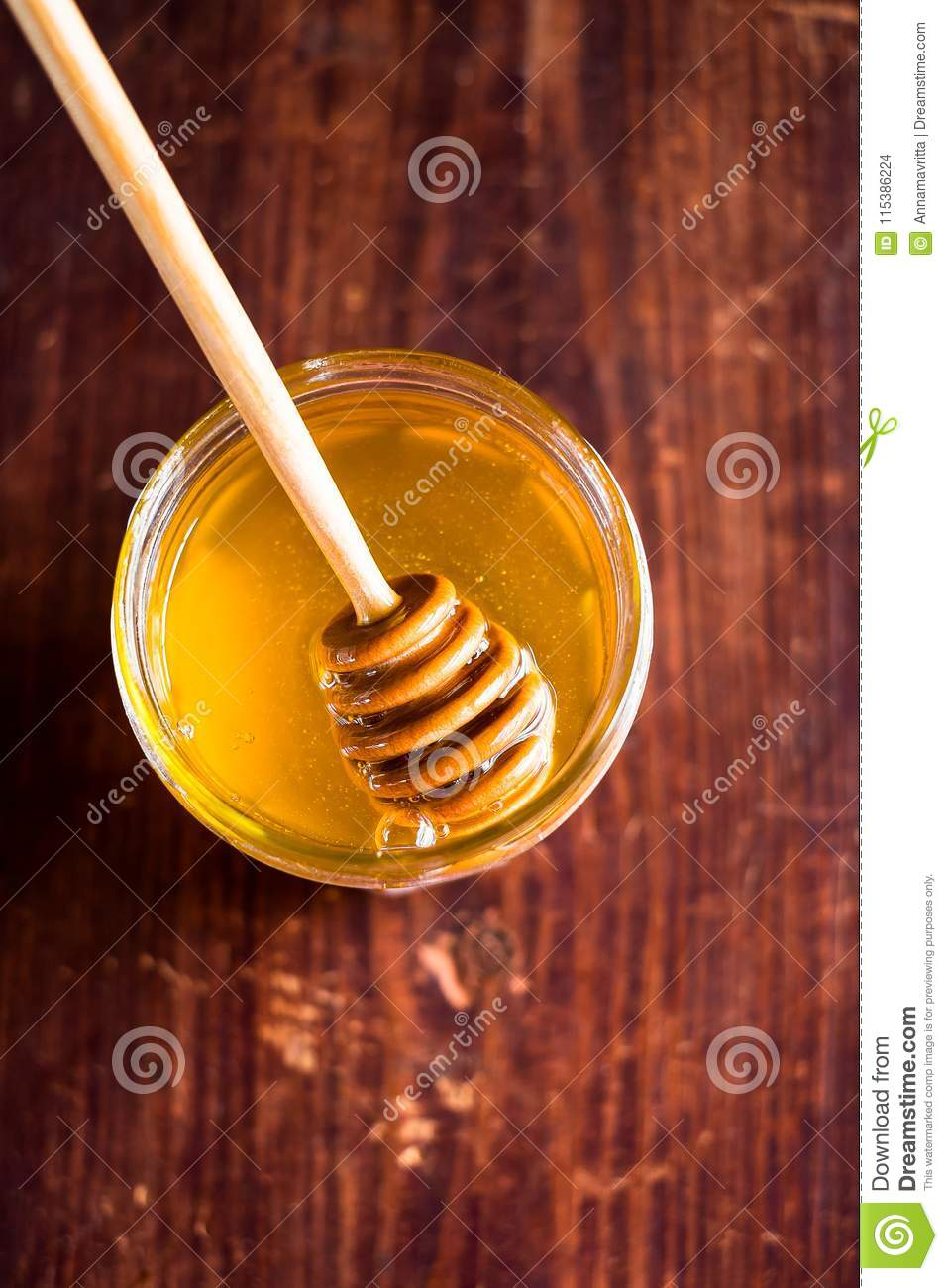 Aromatic honey with wooden honey dipper in a jar on a wooden table, selective focus, closeup. Healthy and organic food option. Ima