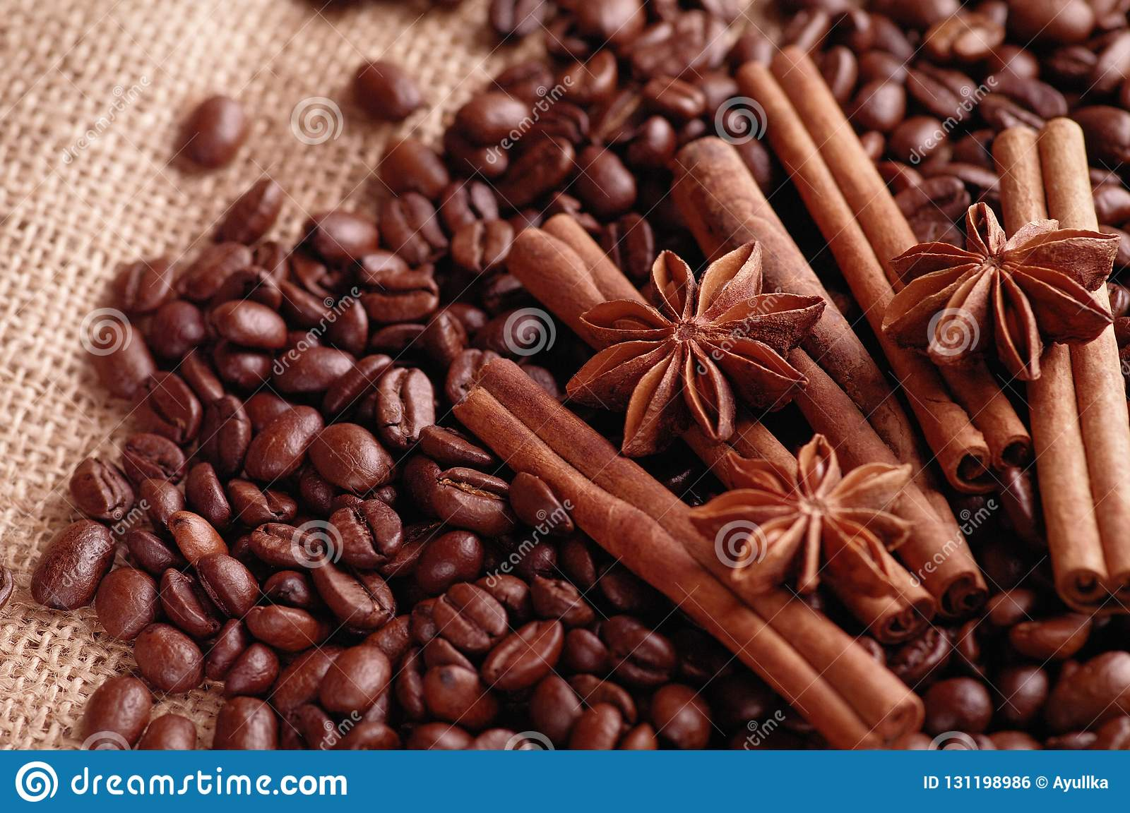 Aromatic roasted coffee beans and anis or badian, sticks of natural cinnamon on background close up