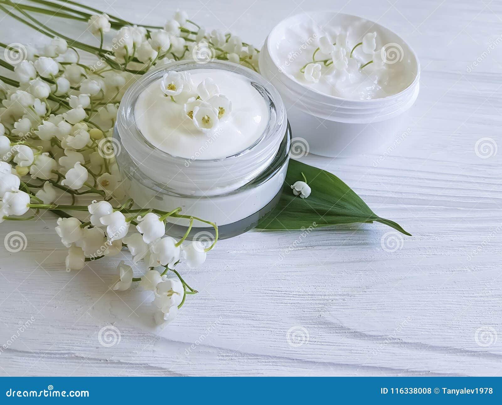 Aromatische rustikale Schönheit der kosmetischen Maiglöckchenentspannungs-Sahnesalbe auf einem weißen hölzernen Hintergrund